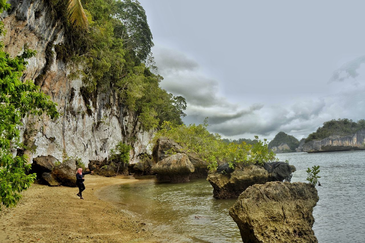 rock - object, rock formation, water, nature, real people, day, beauty in nature, full length, scenics, one person, leisure activity, outdoors, sea, cloud - sky, tranquility, mountain, men, sky, cliff, lifestyles, cave, adventure, tree, one man only, adult, people