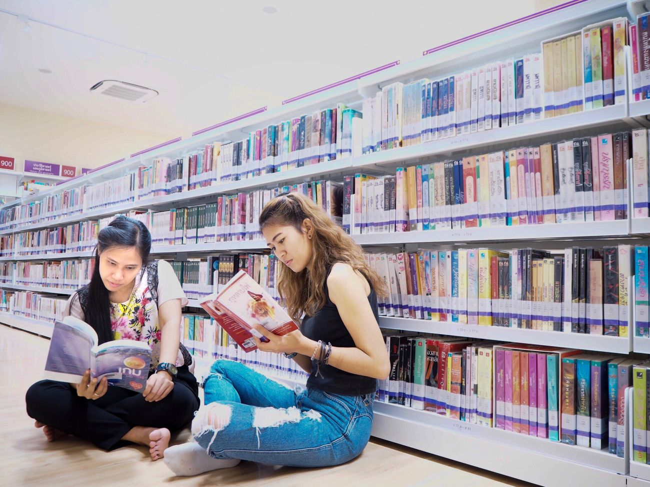 📕📗📘📙📔📒📓 Sitting Book Education Bookshelf Student Learning Indoors  University Student Library Togetherness Two People University Casual Clothing Young Adult Cross-legged Young Women Wireless Technology Holding Full Length Only Women