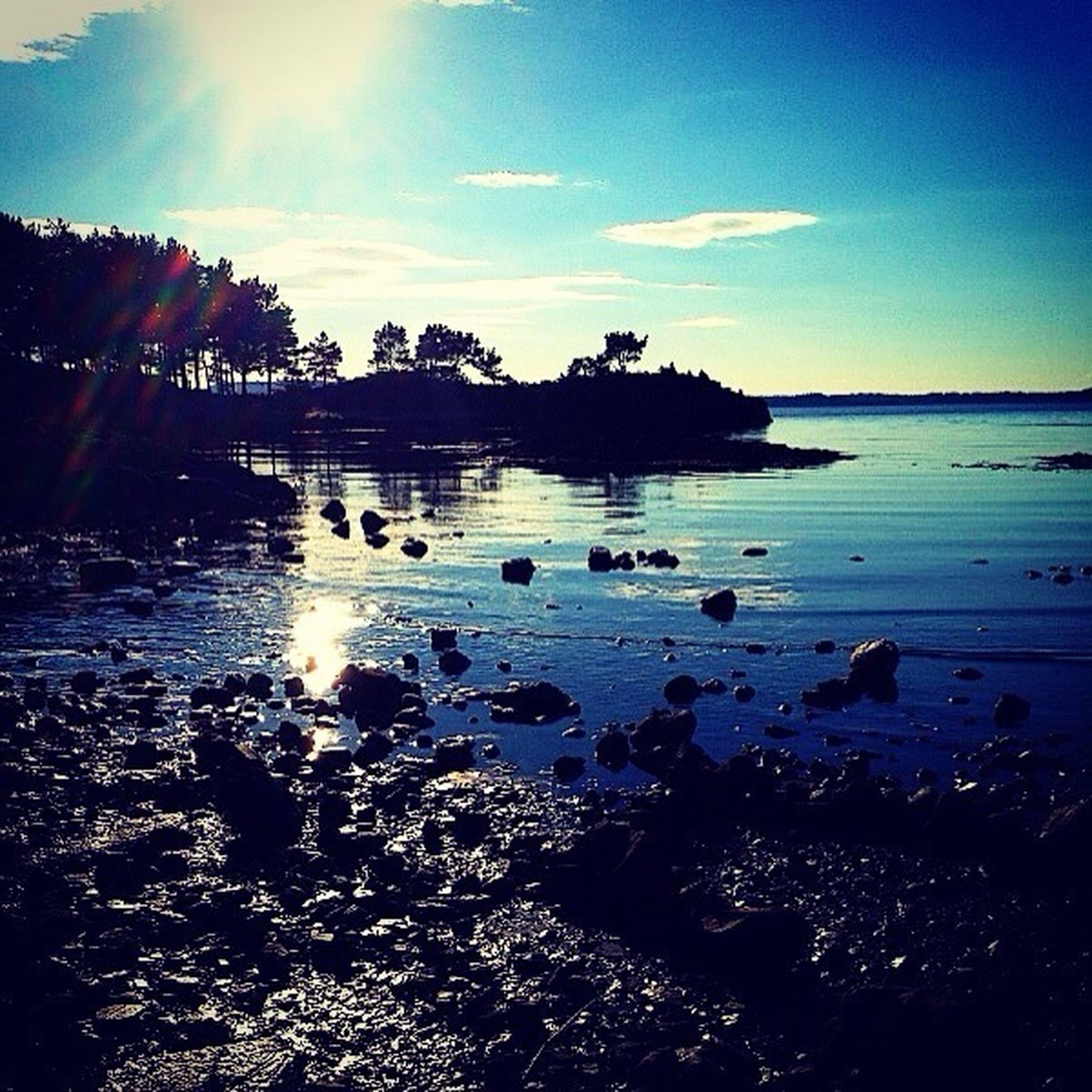 water, sea, beach, sky, tranquil scene, shore, scenics, tranquility, sunset, beauty in nature, sun, reflection, horizon over water, sunlight, nature, silhouette, idyllic, sunbeam, sand, coastline