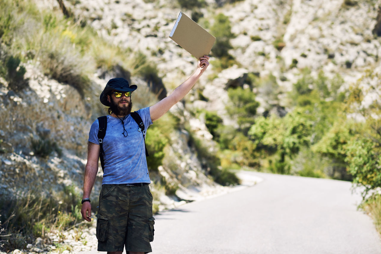 Hiker Standing On Road Against Mountain