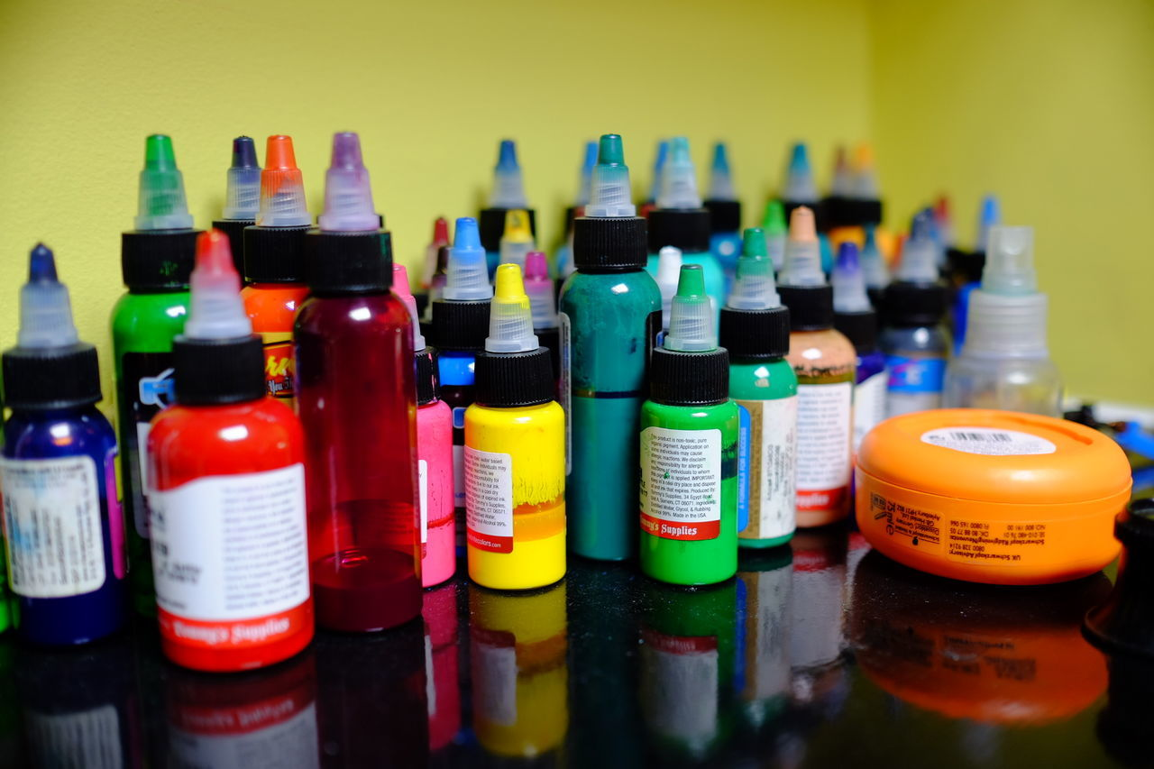 Close-Up Of Colorful Tattoo Ink Bottles On Glass Table