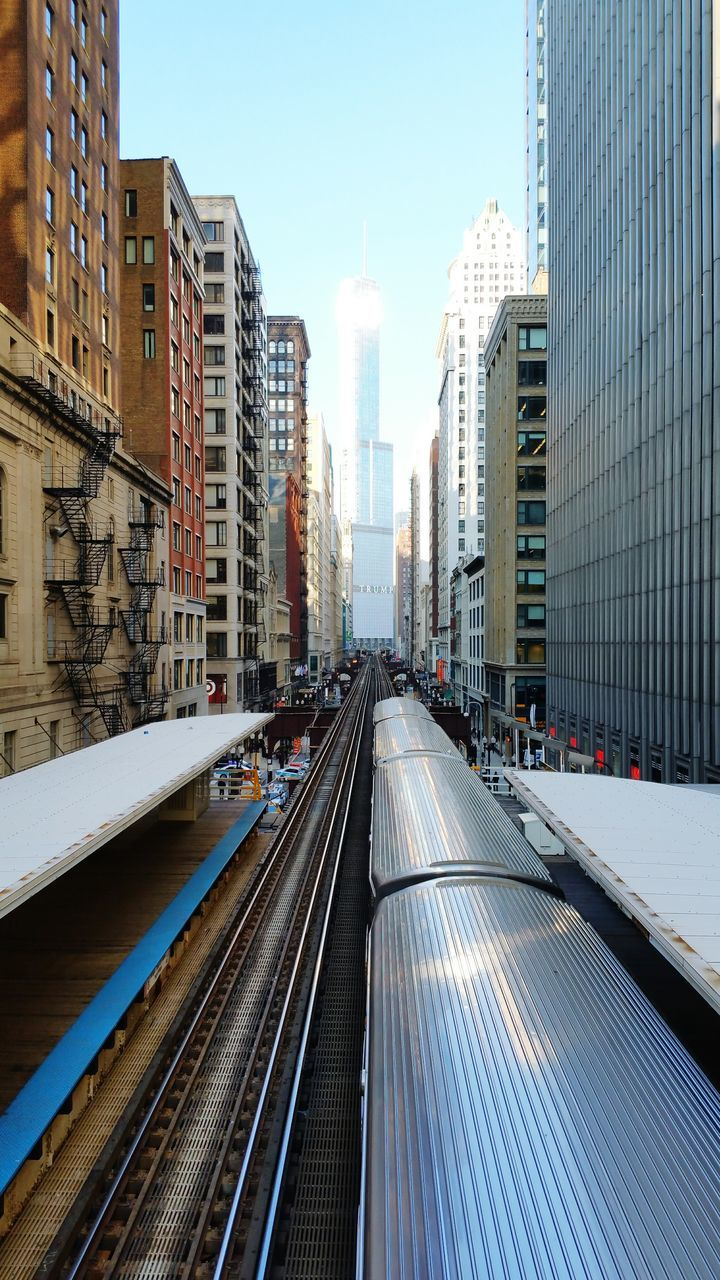 transportation, architecture, built structure, building exterior, the way forward, diminishing perspective, city, vanishing point, railroad track, mode of transport, high angle view, sky, clear sky, day, long, blue, travel, no people, outdoors, city life