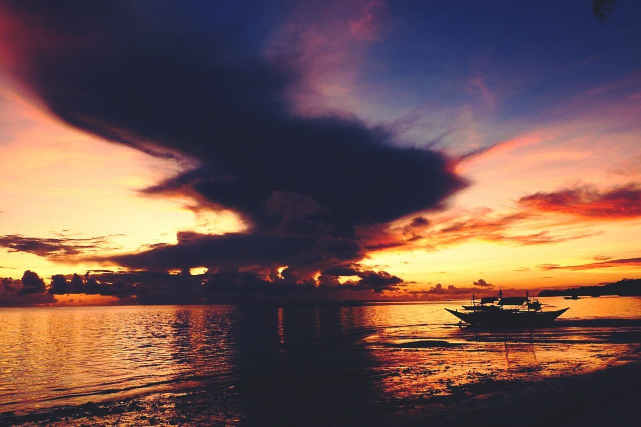sunset, nautical vessel, sky, water, transportation, cloud - sky, silhouette, mode of transport, scenics, nature, boat, beauty in nature, sea, orange color, reflection, tranquility, tranquil scene, waterfront, outdoors, moored, horizon over water, no people, jet boat, sailing, longtail boat, outrigger