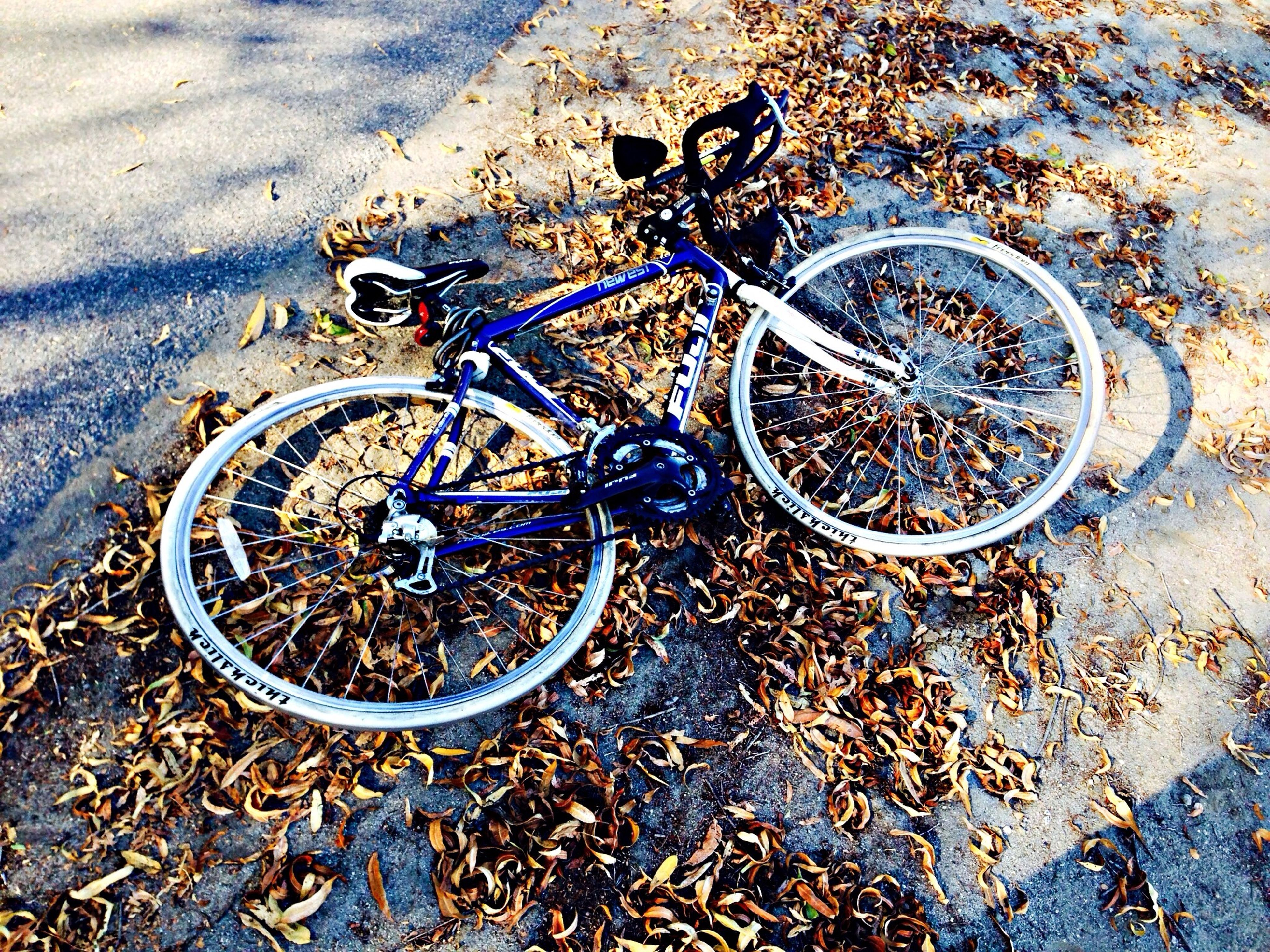 bicycle, transportation, mode of transport, land vehicle, high angle view, stationary, wheel, parked, street, parking, tire, day, outdoors, metal, no people, abandoned, messy, sunlight, close-up, asphalt