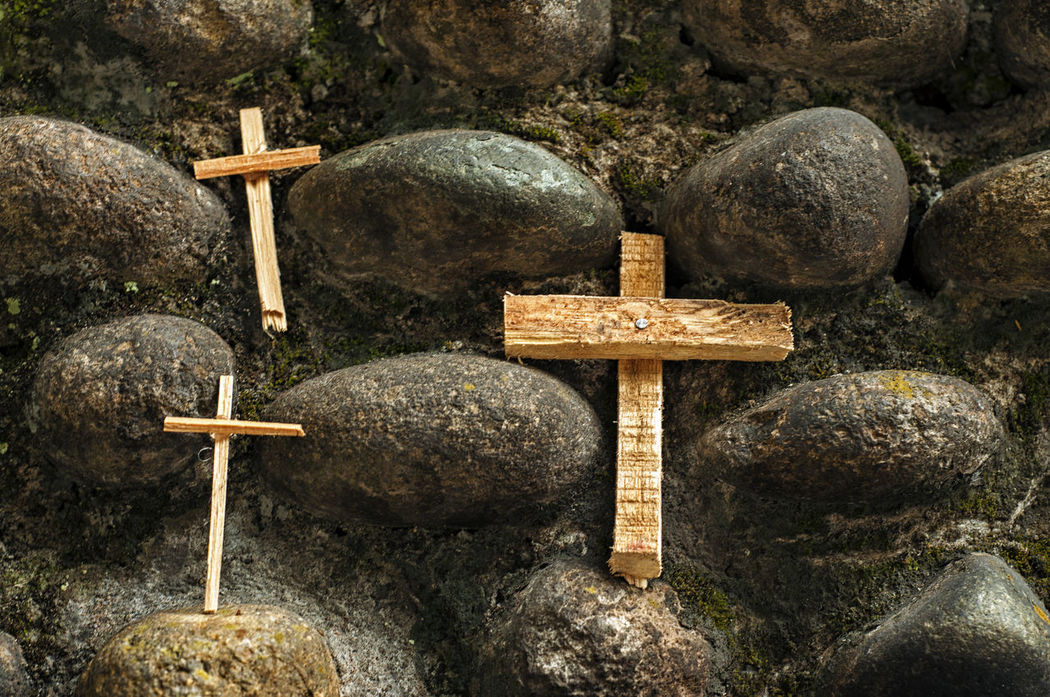 Three wood crosses on a stone wall. Background Catholic Christianity Close-up Colombia Cross Icon Nature Outdoors Popayán Religion Spirituality Stone Symbol Tranquility Wood