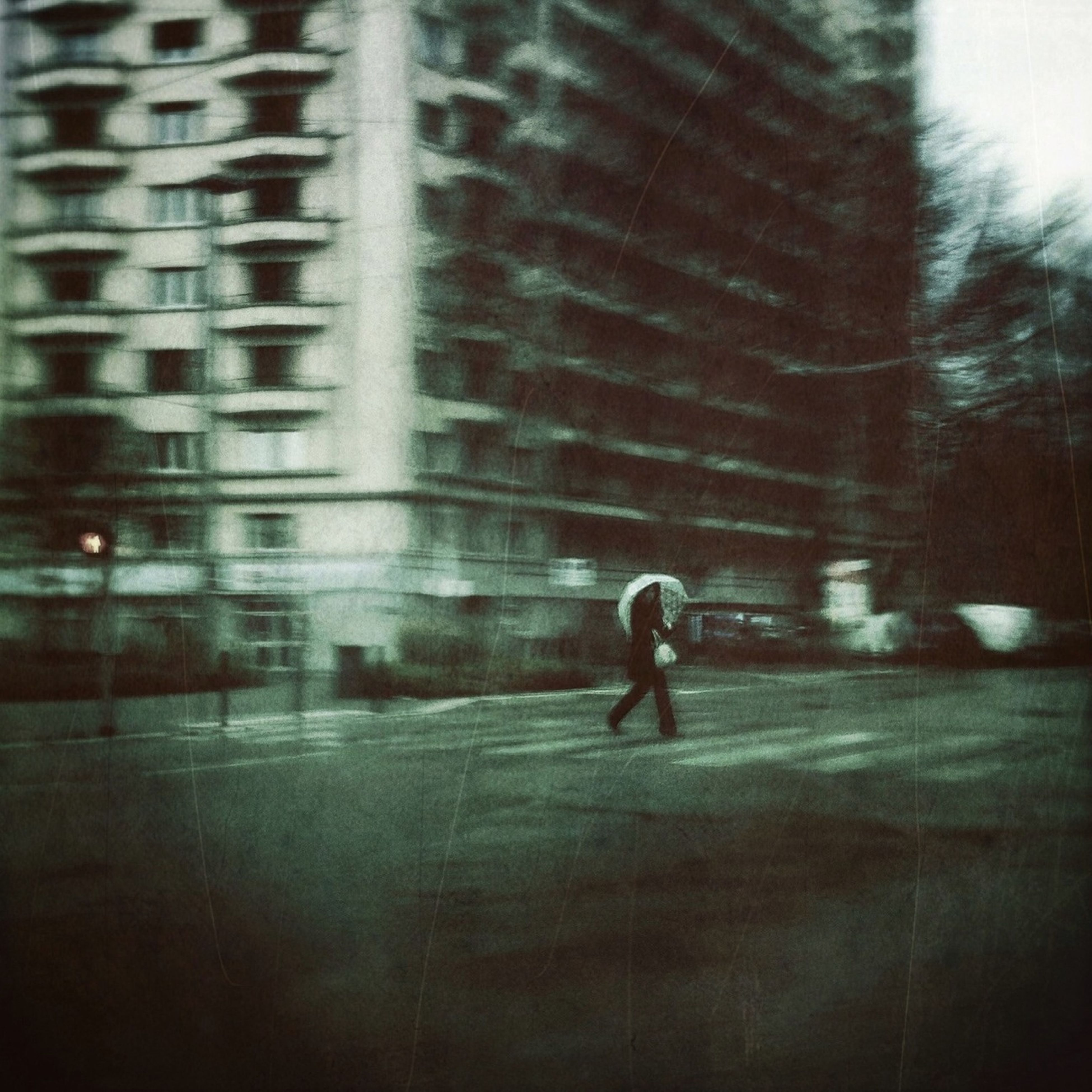 street, built structure, building exterior, architecture, walking, road, rain, transportation, full length, city, blurred motion, wet, on the move, motion, window, sidewalk, unrecognizable person, day