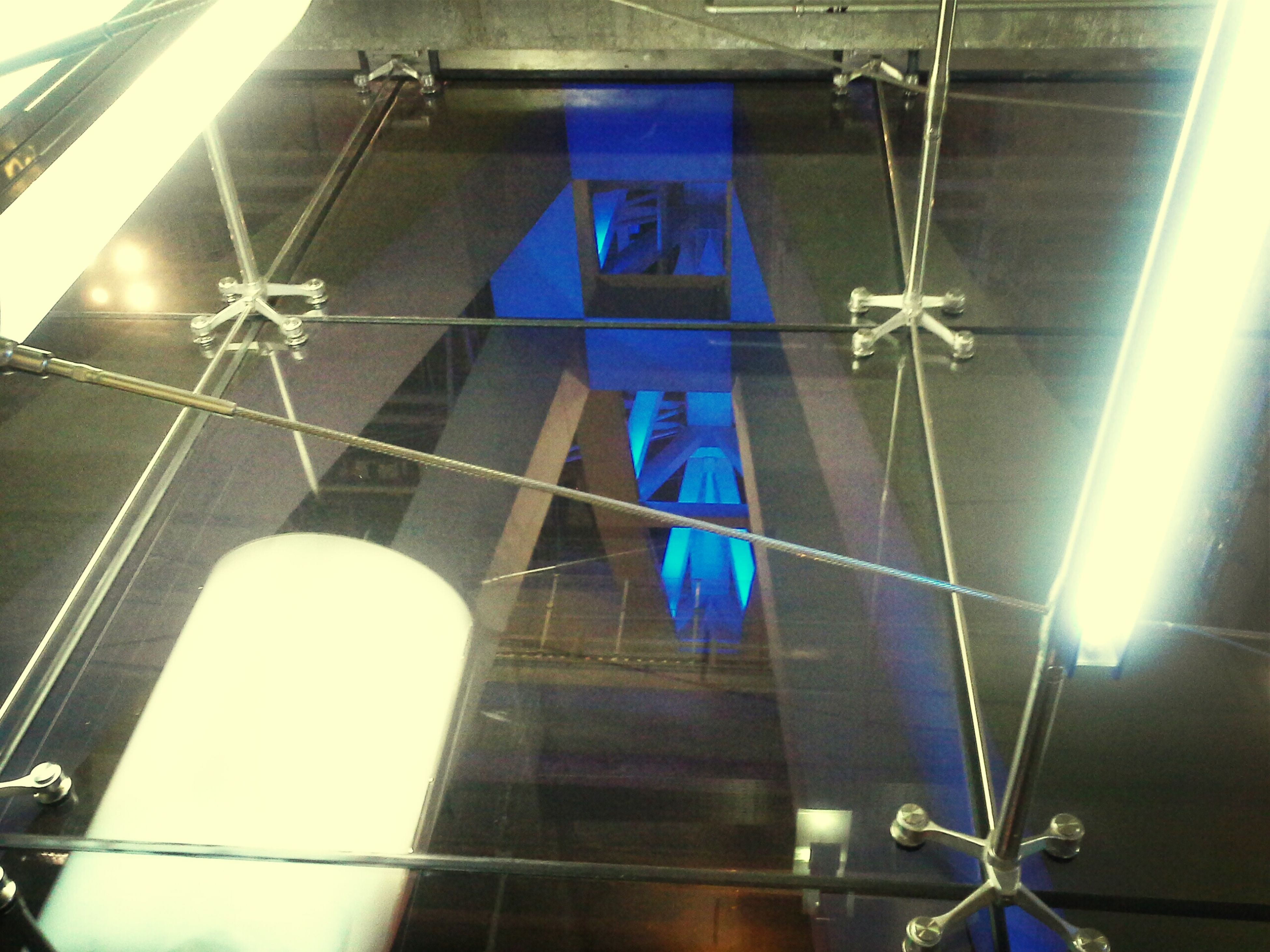 indoors, low angle view, built structure, architecture, hanging, ceiling, lighting equipment, glass - material, window, reflection, illuminated, building exterior, wall - building feature, technology, blue, no people, building, electricity, modern, sunlight