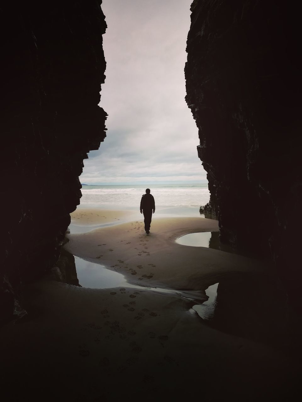 rock formation, sea, silhouette, full length, beach, nature, rock - object, one person, sand, sky, cave, beauty in nature, scenics, real people, tranquility, horizon over water, water, sunset, men, outdoors, day, people