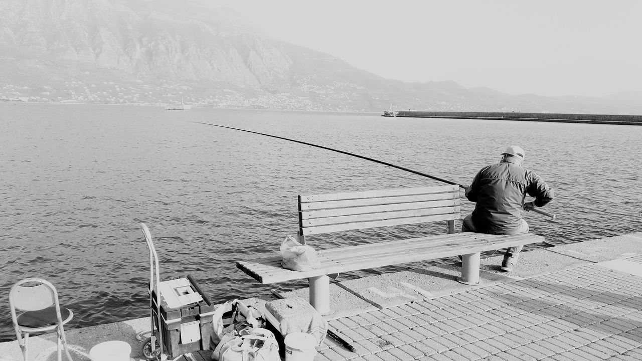 Rear View Of Man Fishing While Sitting On Bench At Promenade By Sea