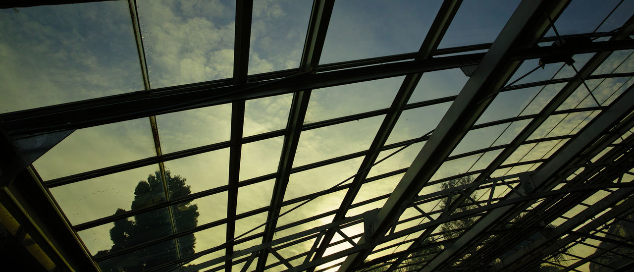 window, glass - material, low angle view, sky, day, reflection, built structure, indoors, architecture, modern, no people, cloud - sky, skyscraper, building exterior, close-up