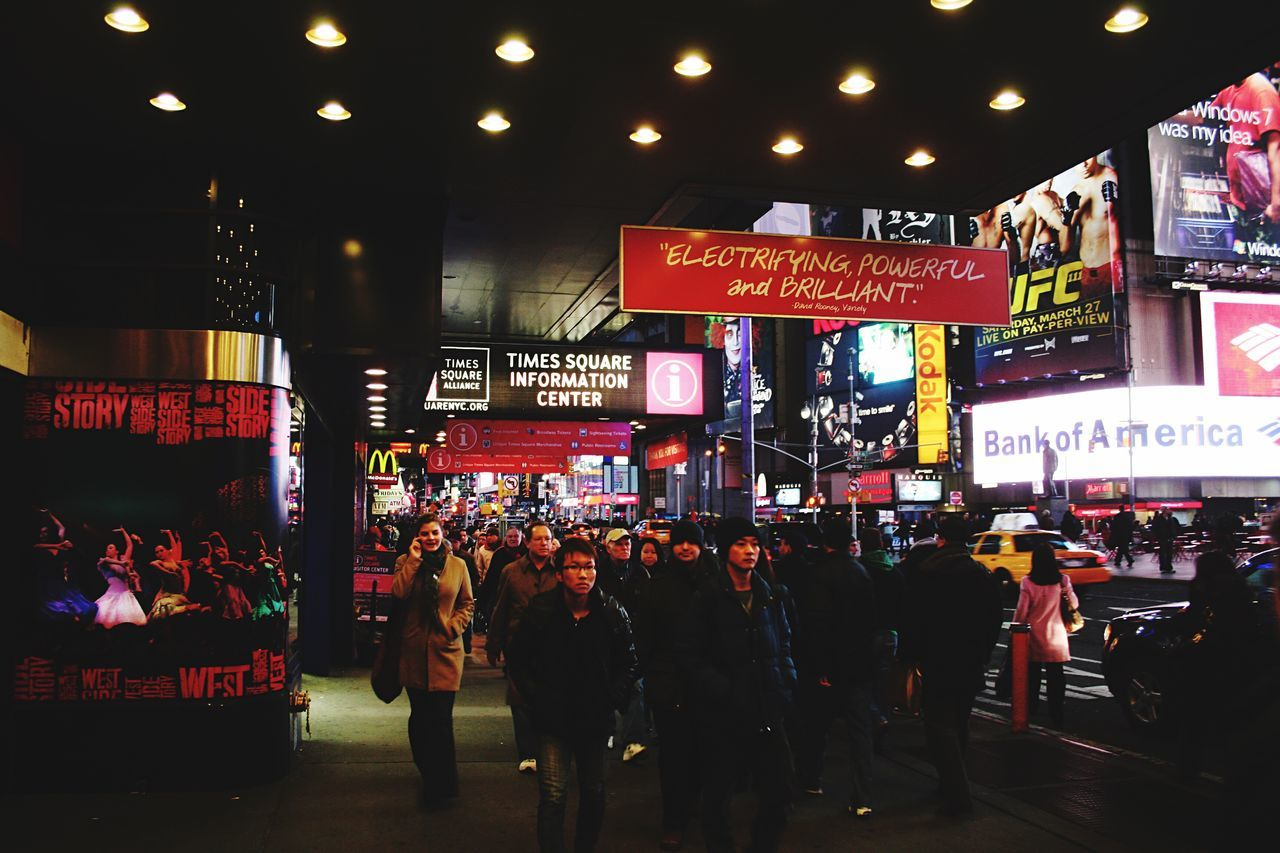 text, illuminated, large group of people, communication, night, men, advertisement, built structure, crowd, city, architecture, real people, building exterior, women, store, lifestyles, outdoors, neon, people
