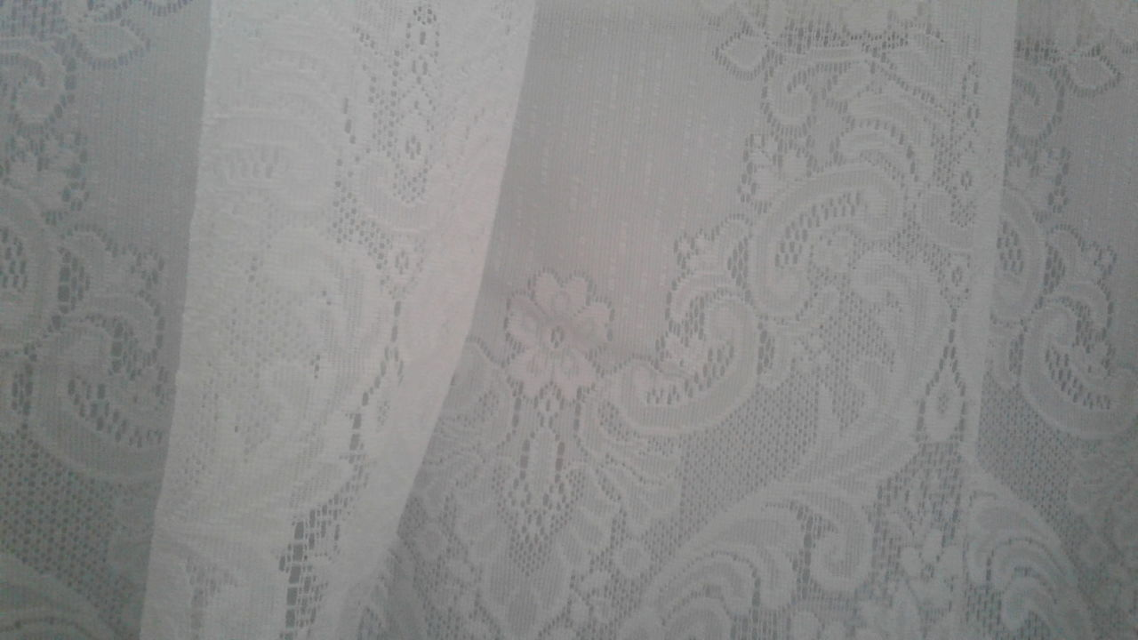 White lace hanging against a pale gray background in the early morning light. Full Frame Lace White White Lace No People Close-up Indoors  Day Backgrounds White Background Fabric Romantic Vintage Morning Light Lifestyle Photography White On White Mobile Photography