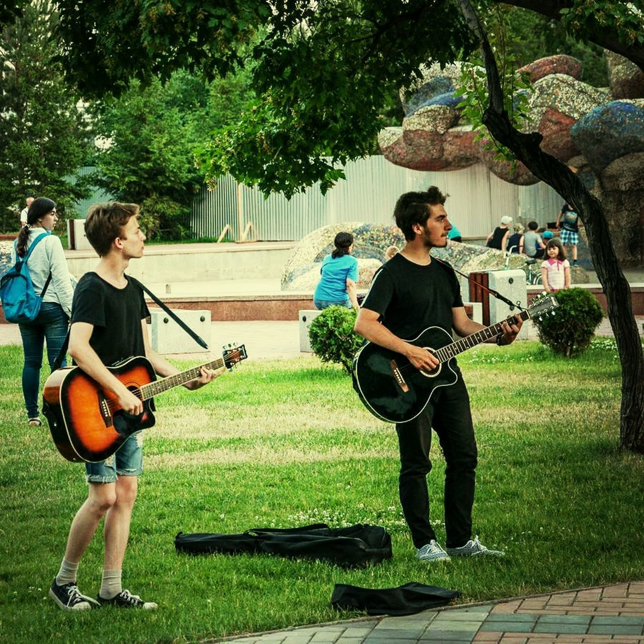 guitar, music, playing, musical instrument, full length, musician, performance, string instrument, plucking an instrument, arts culture and entertainment, leisure activity, day, casual clothing, togetherness, electric guitar, tree, skill, musical instrument string, outdoors, standing, real people, young adult, people, adult, adults only