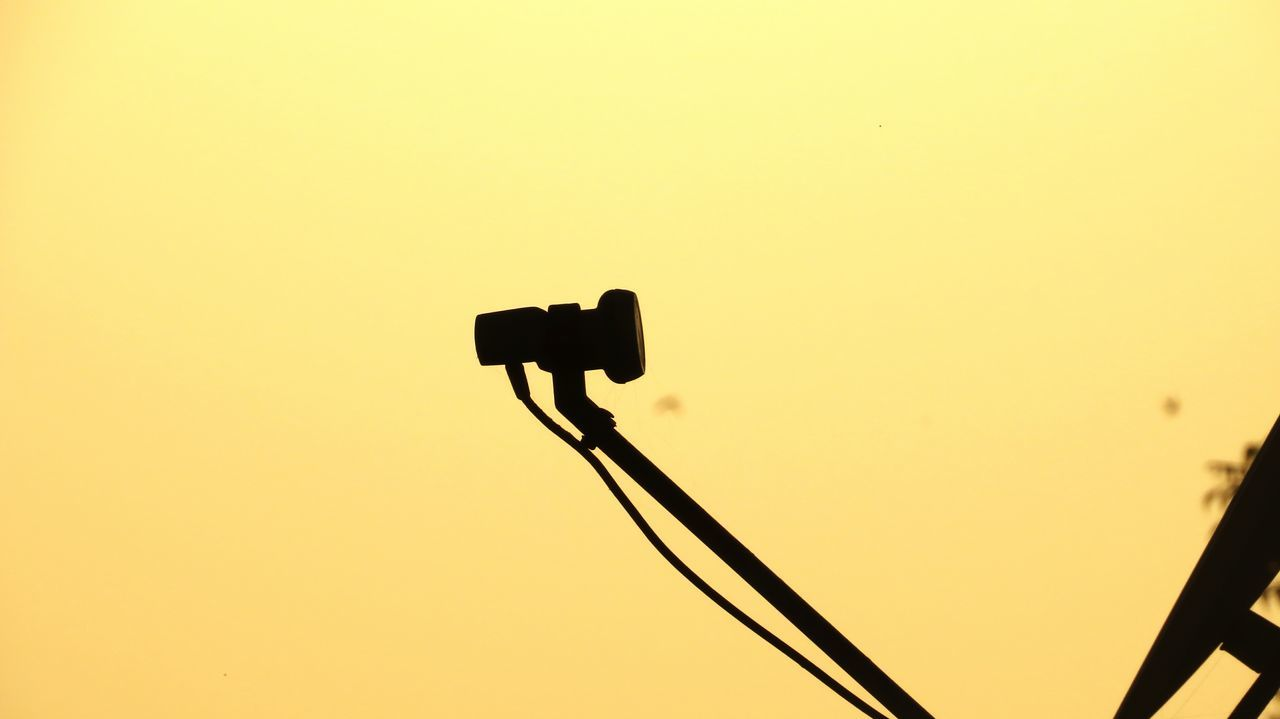 sunset, silhouette, low angle view, technology, copy space, communication, no people, connection, street light, outdoors, stoplight, clear sky, signal, illuminated, yellow, nature, bird, wireless technology, sky, day, close-up