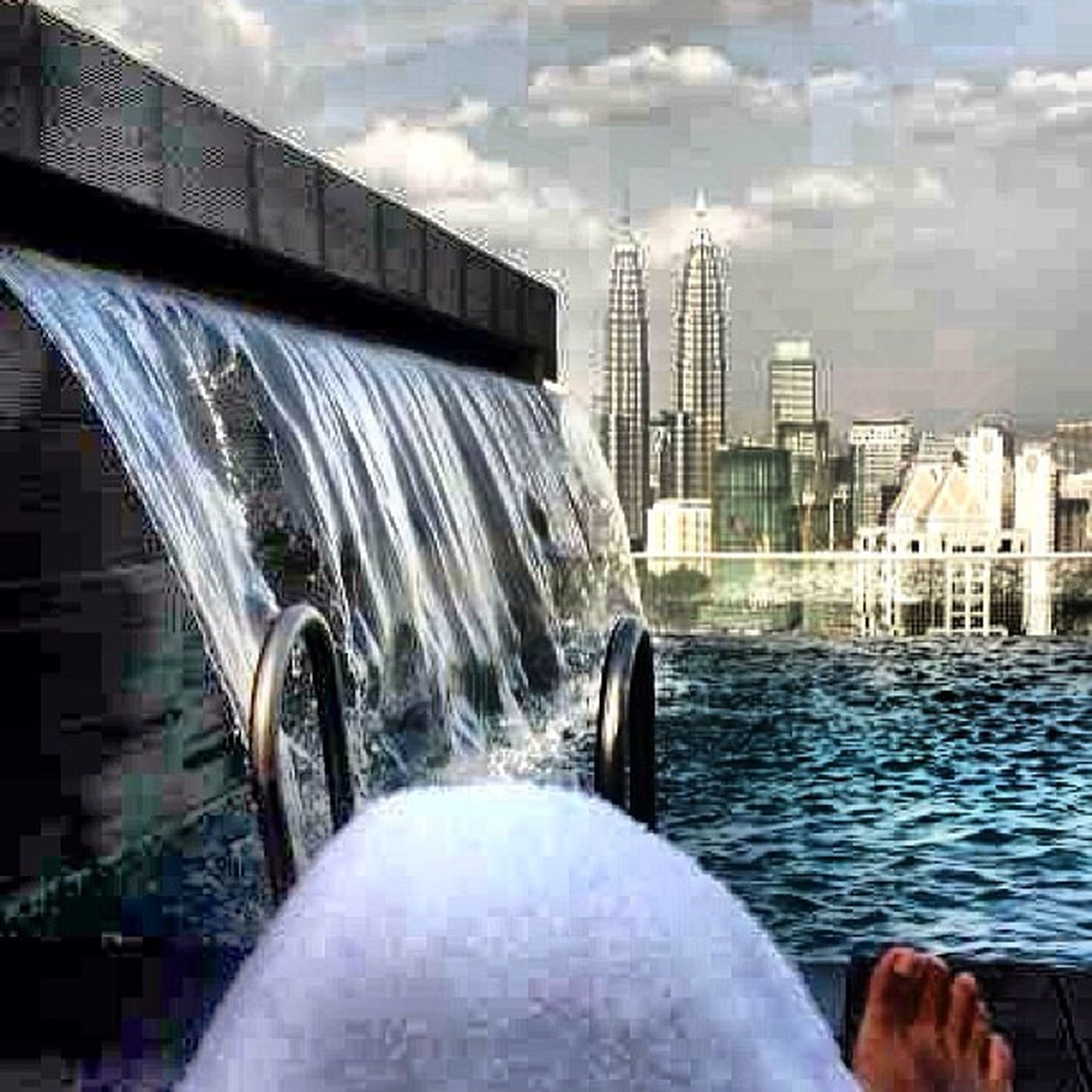 water, building exterior, architecture, built structure, city, fountain, splashing, skyscraper, motion, spraying, waterfront, sky, modern, office building, travel destinations, day, city life, outdoors