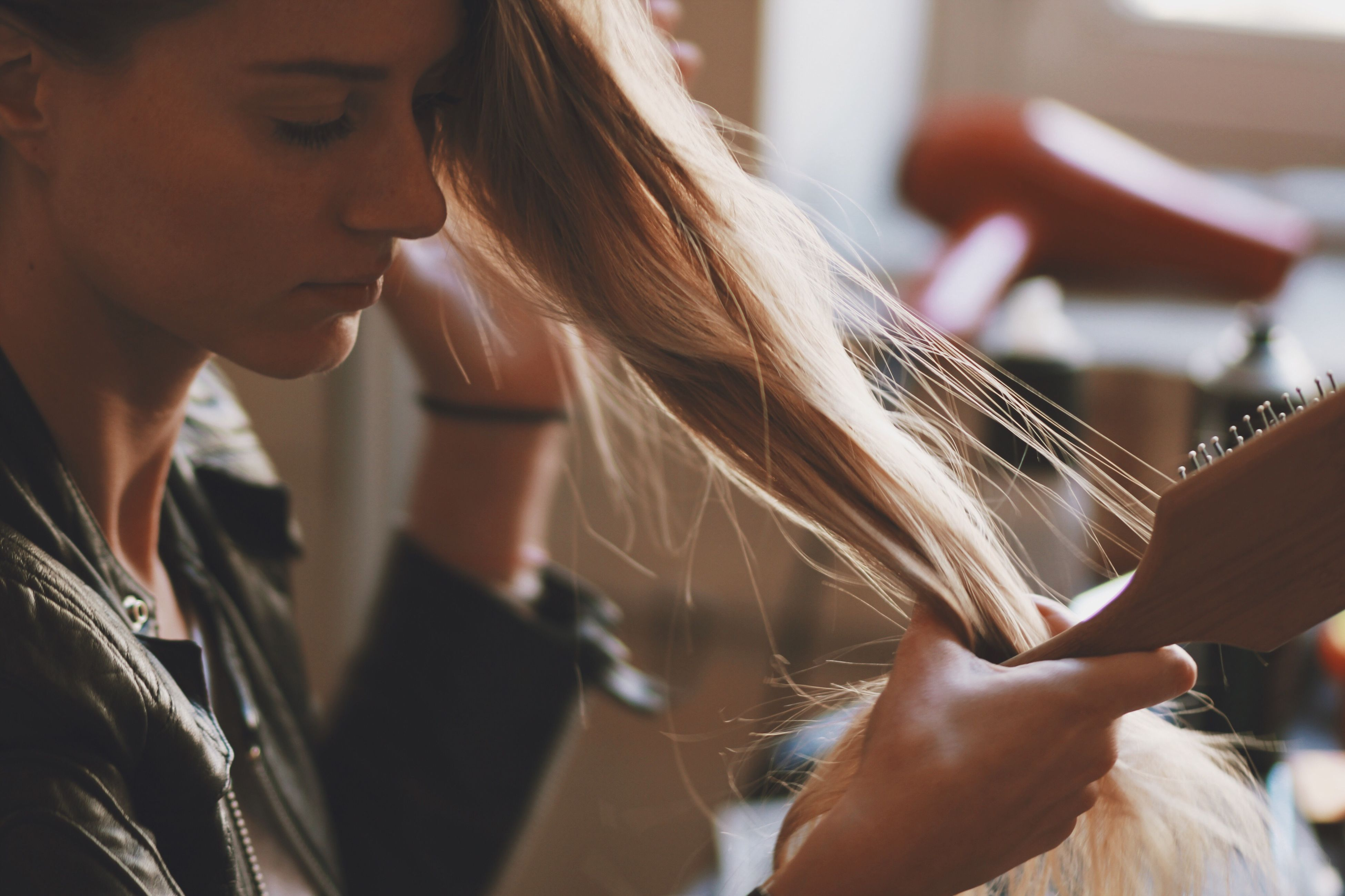holding, leisure activity, lifestyles, person, indoors, long hair, blond hair, focus on foreground, beauty, human hair, selective focus, casual clothing, young adult, looking, hair care