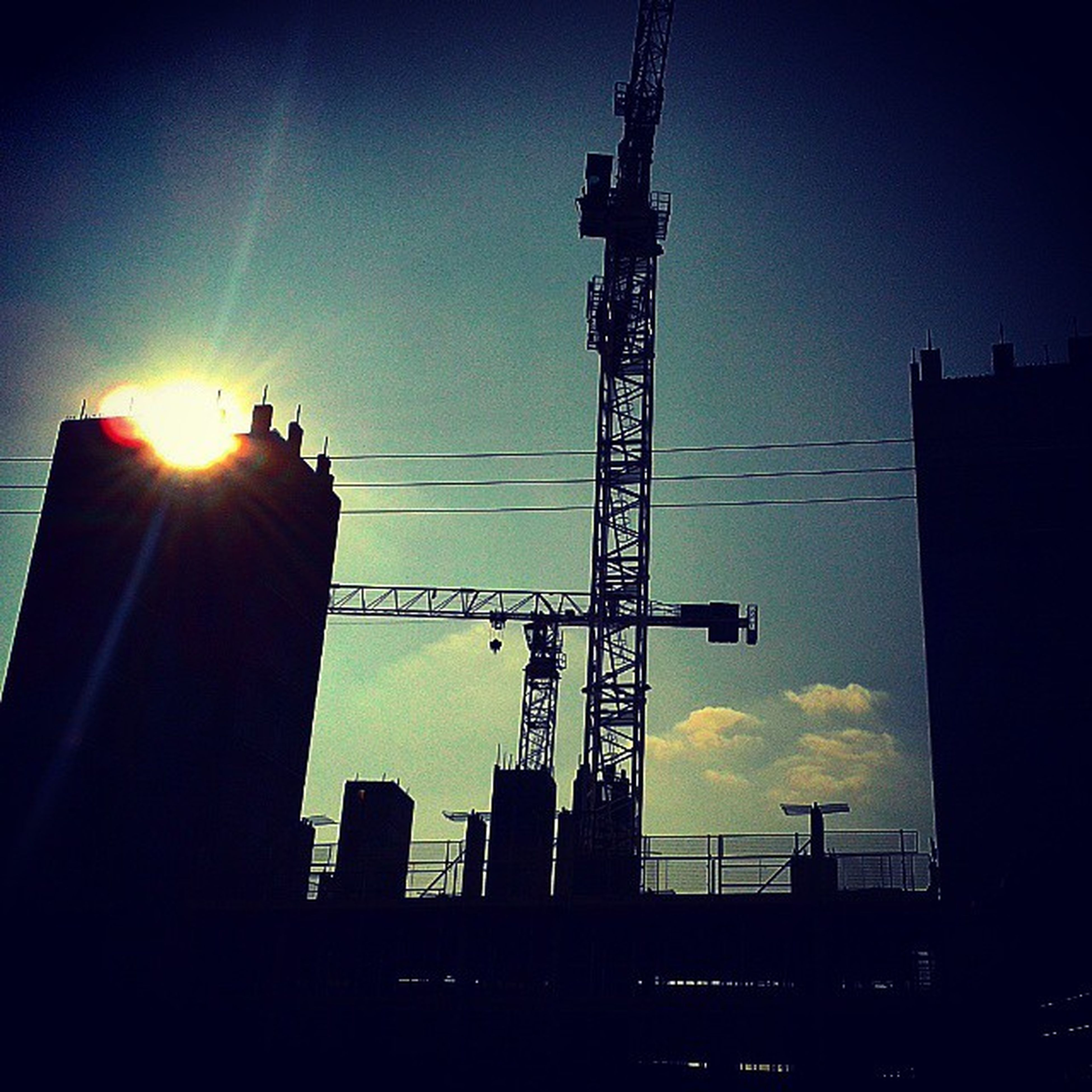 silhouette, sunset, low angle view, crane - construction machinery, built structure, building exterior, architecture, sun, construction site, sky, development, crane, fuel and power generation, technology, sunlight, industry, electricity, tall - high, sunbeam, power line
