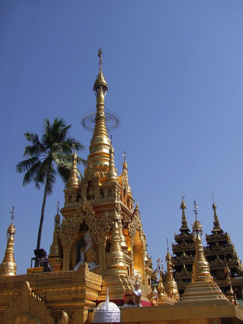Main Building at Yaylel Pagoda Blue Sky Buddha Buddhist Architecture Buddhist Art Buddhist Culture Buddhist Pagoda Buddhist Temple Composition Gold Coloured Gold Stupas Low Angle View Myanmar No People Ornate Design Outdoor Photography Palm Tree Place Of Pilgrimage Place Of Prayer Place Of Worship Religion Spirituality Sunlight And Shade Thanlyin Travel Destination Yaylel Pagoda