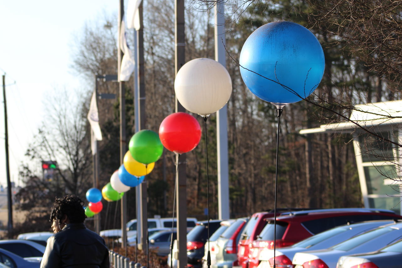 balloon, real people, helium balloon, tree, celebration, built structure, outdoors, architecture, building exterior, day, one person, multi colored