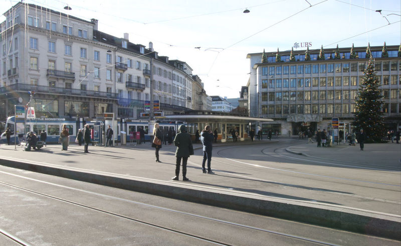 Paradeplatz - Bahnhofstrasse, Zurich. Located in the middle of Zurich's Bahnhofstrasse, between the main train station (Hauptbahnhof) and Zurichsee (Lake Zurich), Paradeplatz is an important tram junction connecting the north, east, south and west of 'Switzerland's Little Big City'. Zurich Transport (ZVV) tram maps and free copies of the latest Zurich in Your Pocket travel guide are available at Paradeplatz to help tourists make the most of their visit to Zurich. http://pics.travelnotes.org/ Bahnhofstrasse Casual City Façade Going To Work Modern Life Paradeplatz Tourists Tram Stop Transportation Travel Travel Photography UBS Bank Waiting Zürich Buildings Candid Clear Day Daily Life People Real People Street Scene Switzerland Trams Travel Pics