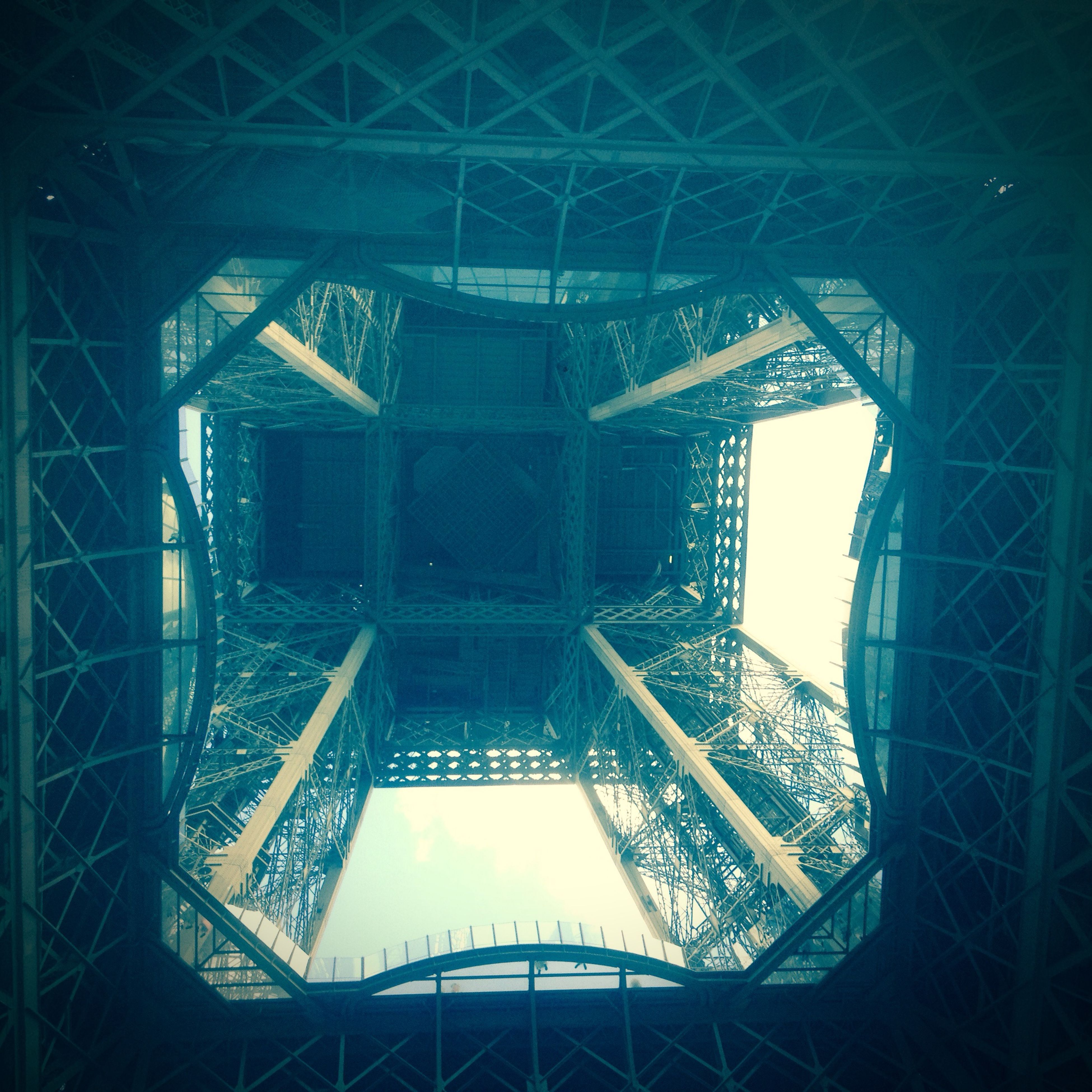 architecture, built structure, low angle view, indoors, building exterior, architectural feature, famous place, modern, tower, city, glass - material, metal, capital cities, international landmark, travel destinations, day, culture, no people, eiffel tower, building