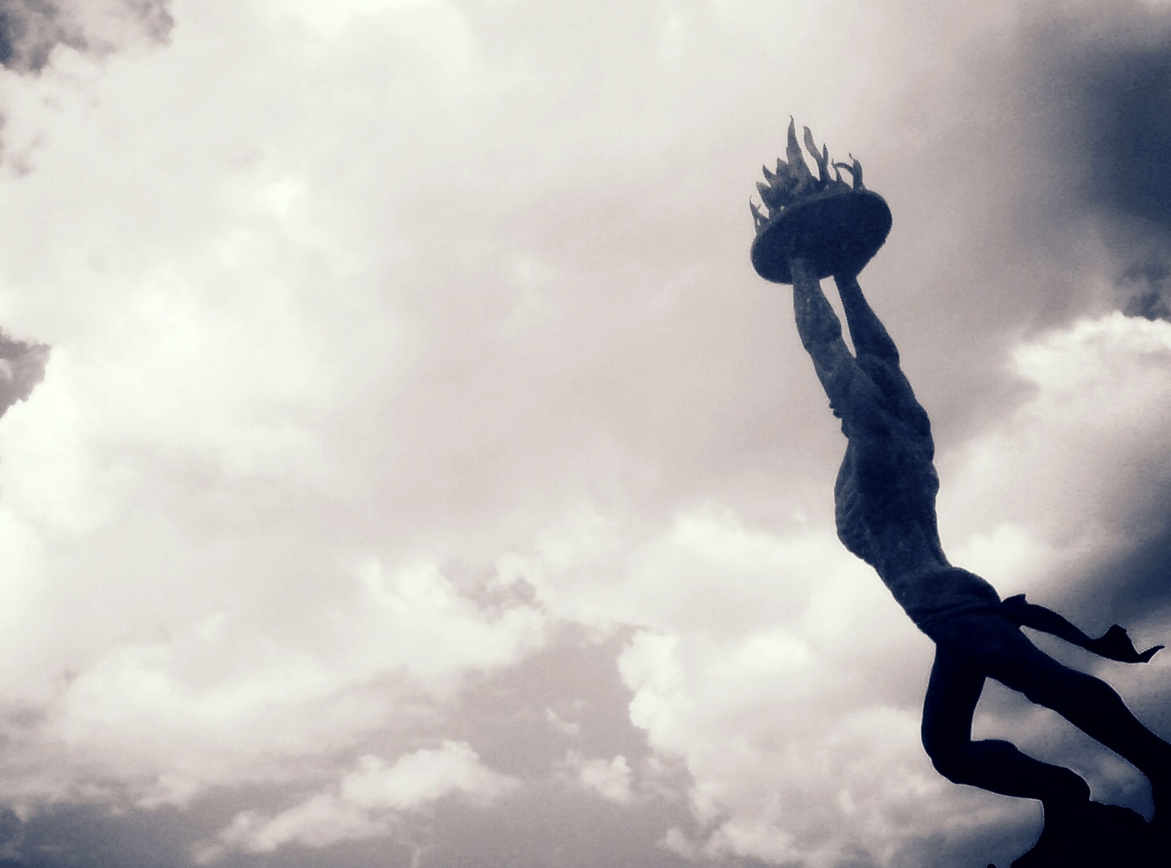 low angle view, sky, cloud - sky, cloudy, statue, human representation, sculpture, cloud, art, art and craft, creativity, silhouette, overcast, weather, day, outdoors, nature, one person