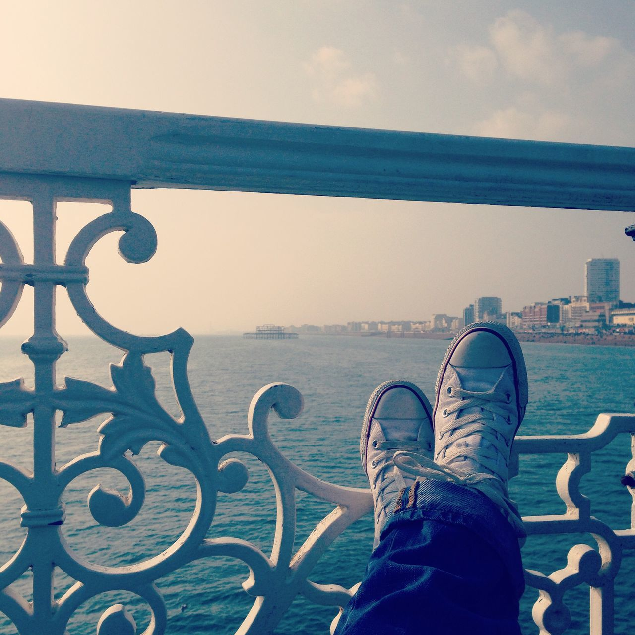 human leg, low section, one person, personal perspective, shoe, real people, human foot, railing, human body part, standing, outdoors, day, sea, lifestyles, sky, women, water, close-up, men, people