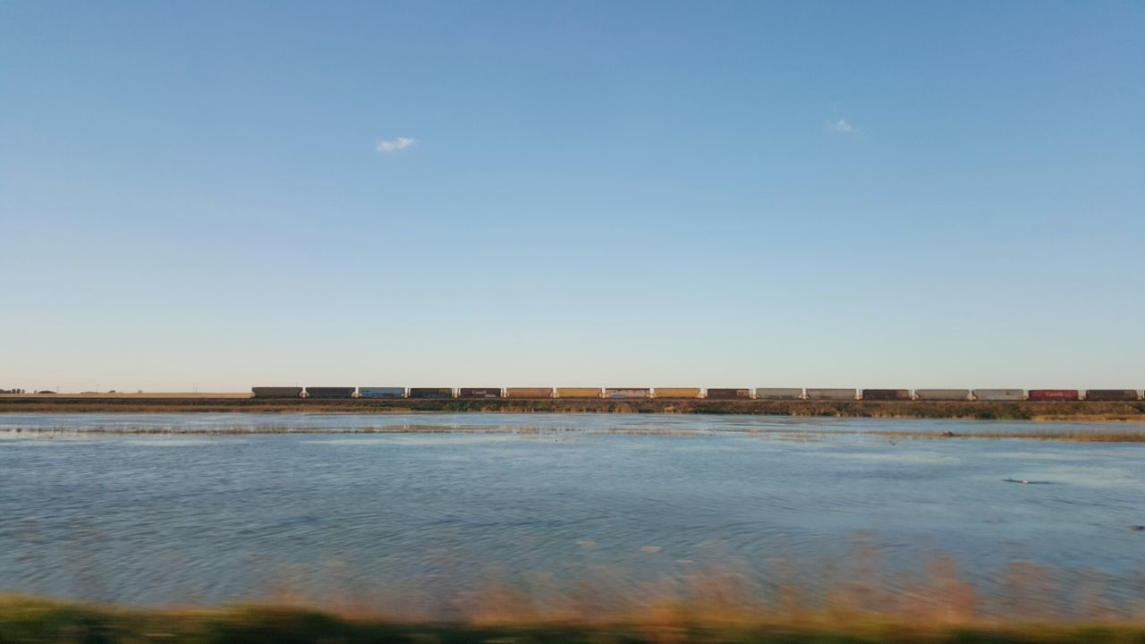 Water Sky Horizontal Outdoors Tranquility No People Clear Sky Day Nature Scenics Train Train Cars Pond Countryside Plains Prarie Prarie Life Flat Transportation Driving Travel