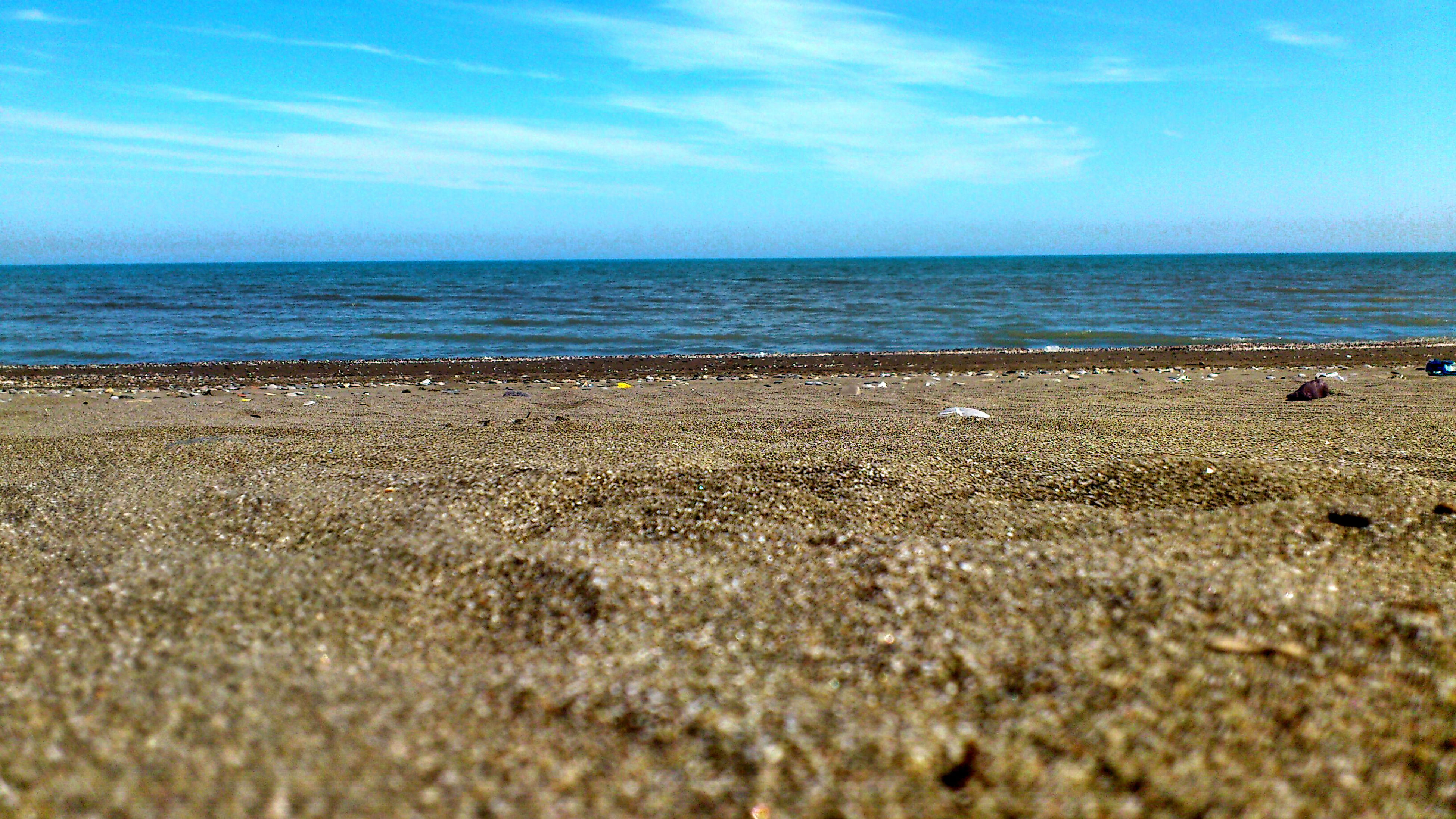 sea, beach, horizon over water, sand, water, sky, shore, tranquil scene, scenics, tranquility, surface level, beauty in nature, nature, blue, idyllic, cloud, wave, pebble, cloud - sky, day