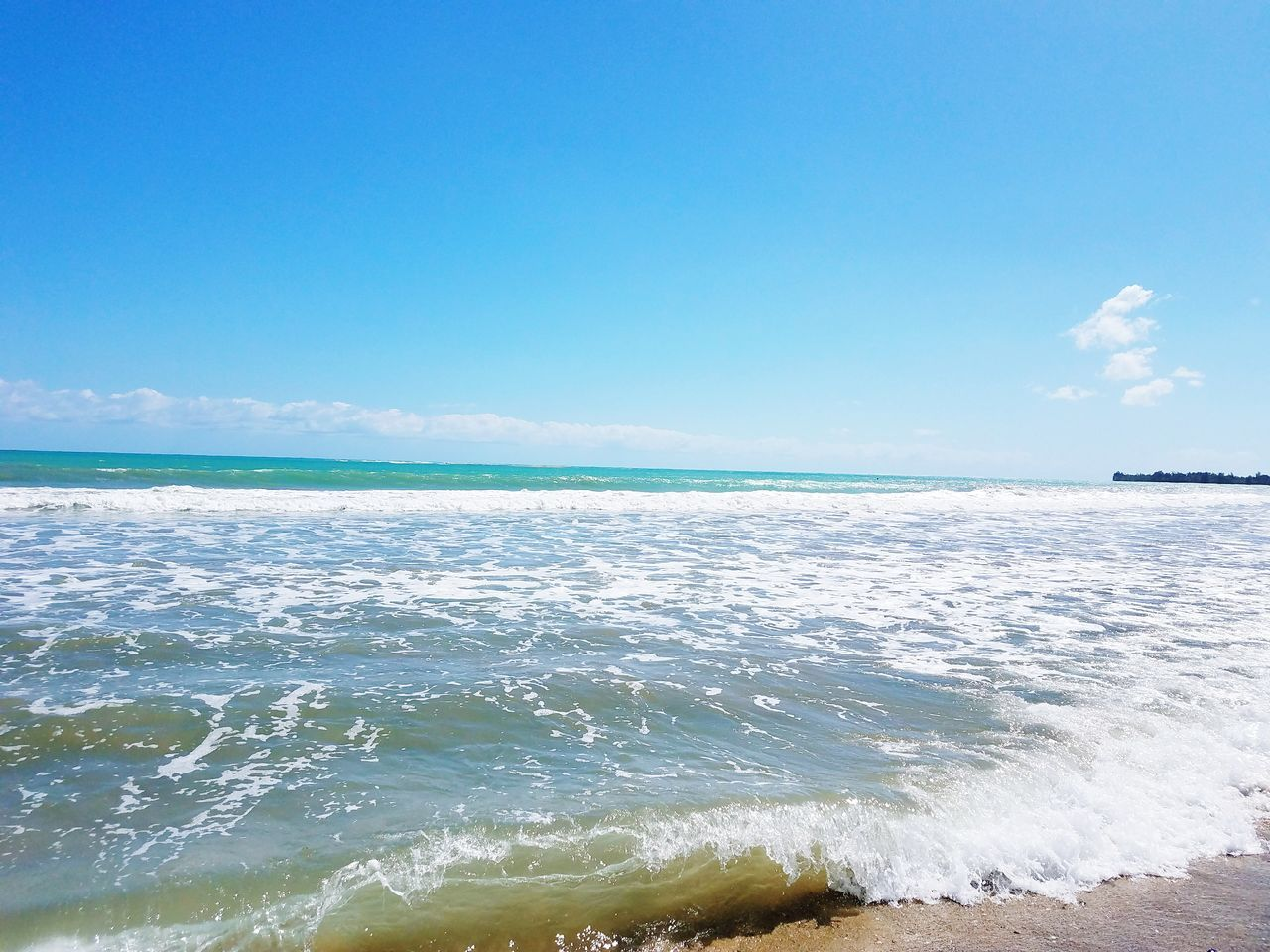 sea, beauty in nature, nature, scenics, water, wave, horizon over water, tranquil scene, surf, beach, tranquility, blue, outdoors, no people, sky, day, motion, sunlight, travel destinations, summer, sand, vacations