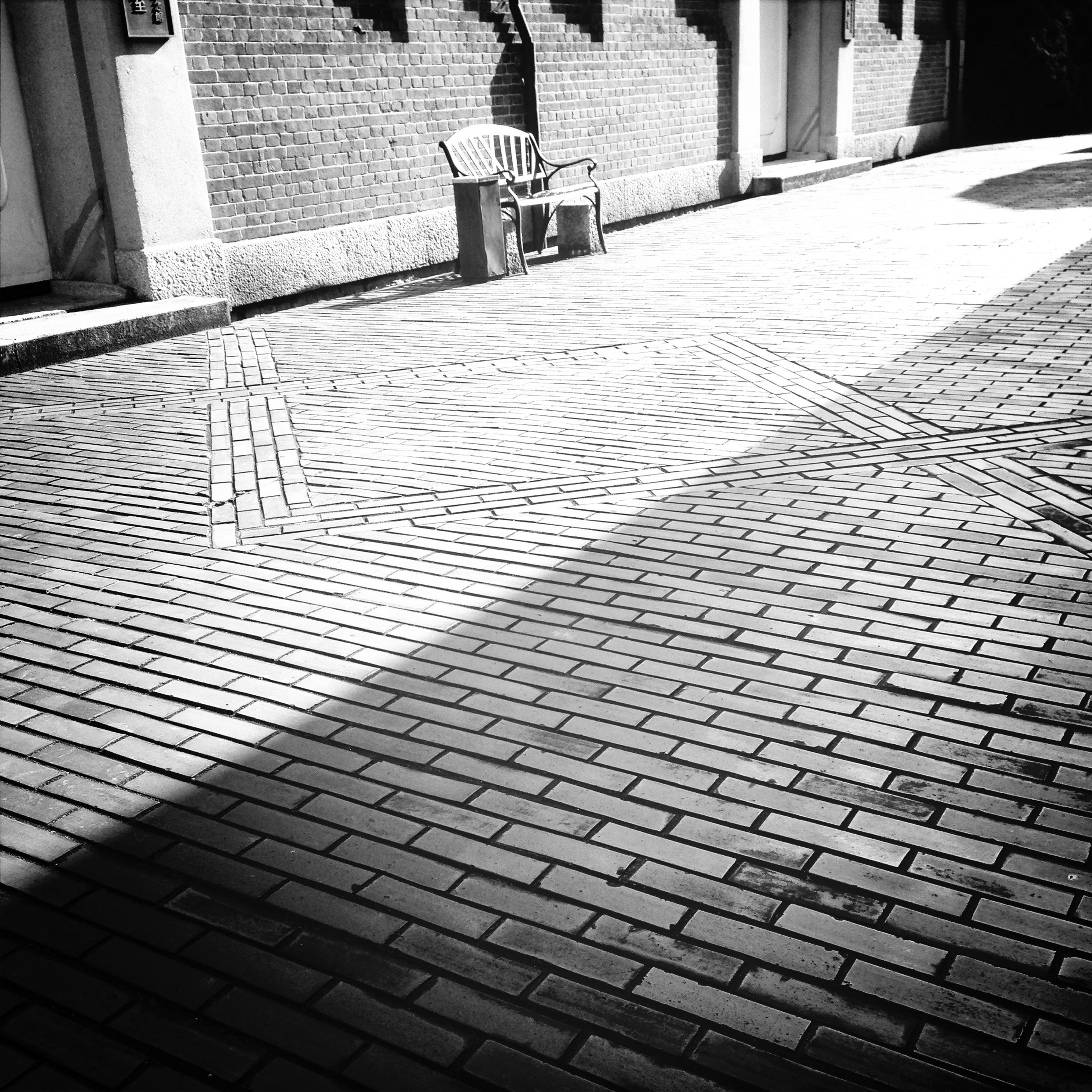 architecture, building exterior, built structure, cobblestone, shadow, pattern, sunlight, street, city, high angle view, the way forward, day, building, outdoors, footpath, sidewalk, no people, walkway, paving stone, empty