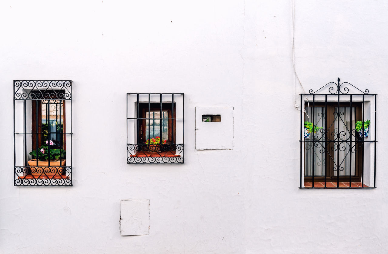 Windows with steel lattice on a whitewashed wall. Andalusian white village. Costa del Sol. Spain Andalucía Exterior Framed Home Lattice Malaga Rustic SPAIN Building Exterior Built Structure Costa Del Sol Decorated Decoration Glass No People Outdoors Pueblo Blanco Residential Building Three Typical House Wall - Building Feature White Village Whitewashed Walls Windows