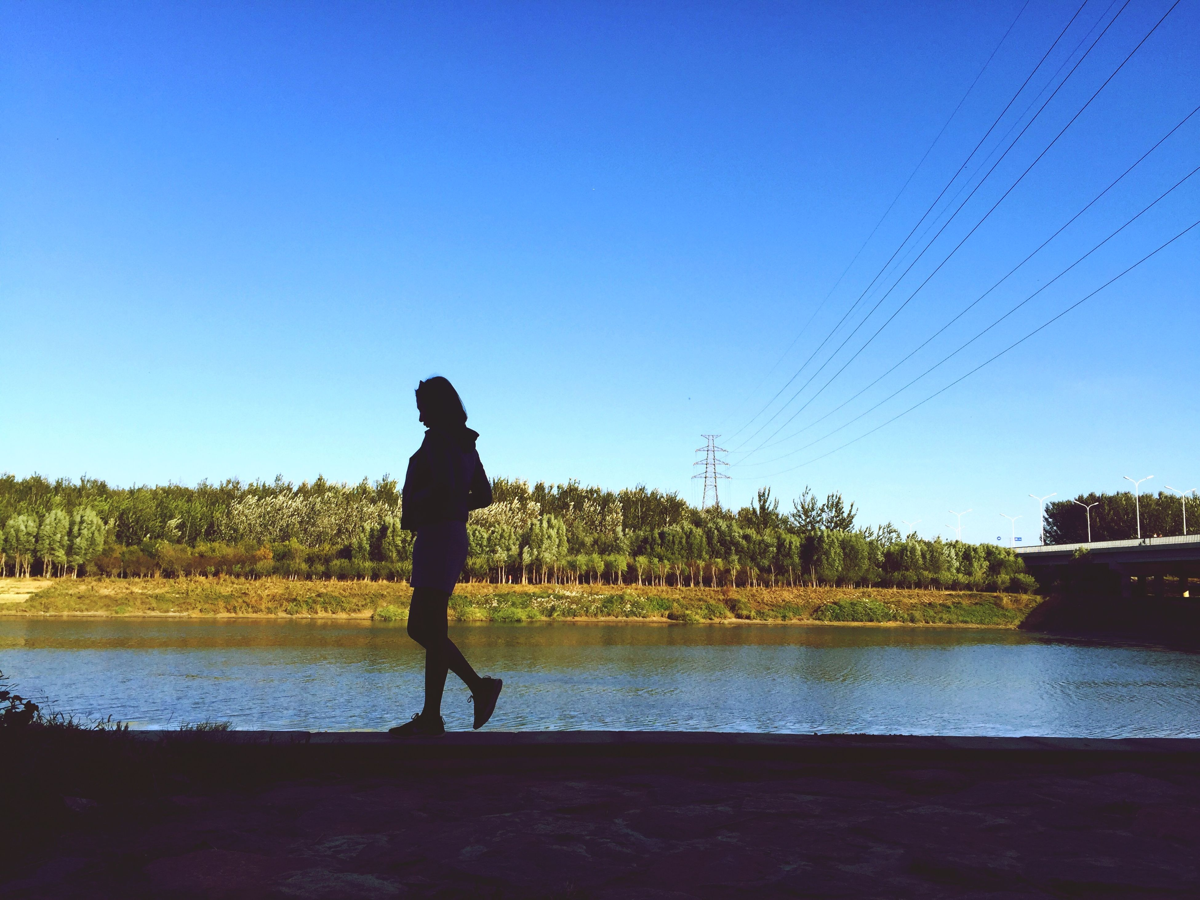 water, clear sky, full length, standing, rear view, lake, blue, lifestyles, leisure activity, copy space, tranquility, silhouette, tranquil scene, men, scenics, reflection, nature, walking