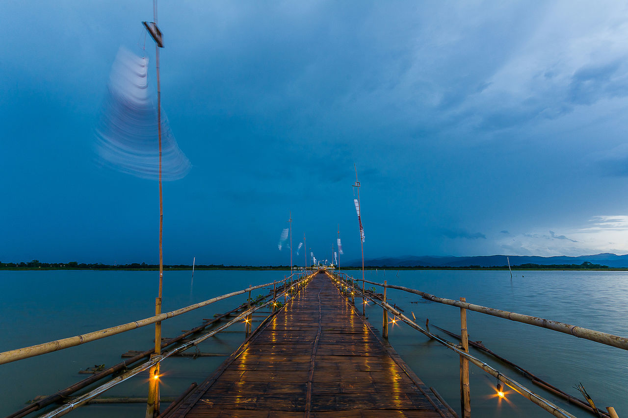 PHAYAO, THAILAND - JULY 19, 2016: The bamboo bridge, The bamboo bridge of Wat Ti Lok Aram temple in kwan phayao off freshwater lake of Thailand. Day is the important Buddhist. ASIA Bamboo Bridge Beauty In Nature Blue Buddhist Cloud Cloud - Sky Diminishing Perspective Idyllic Illuminated Important Kwan Phayao Nature No People Outdoors Scenics Sky Temple Thailand The Way Forward Tranquil Scene Tranquility Vanishing Point Wat Ti Lok Aram Water