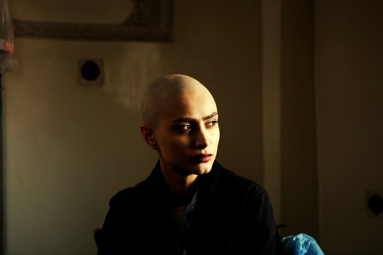 Thoughtful Bald Young Woman With Cancer At Home