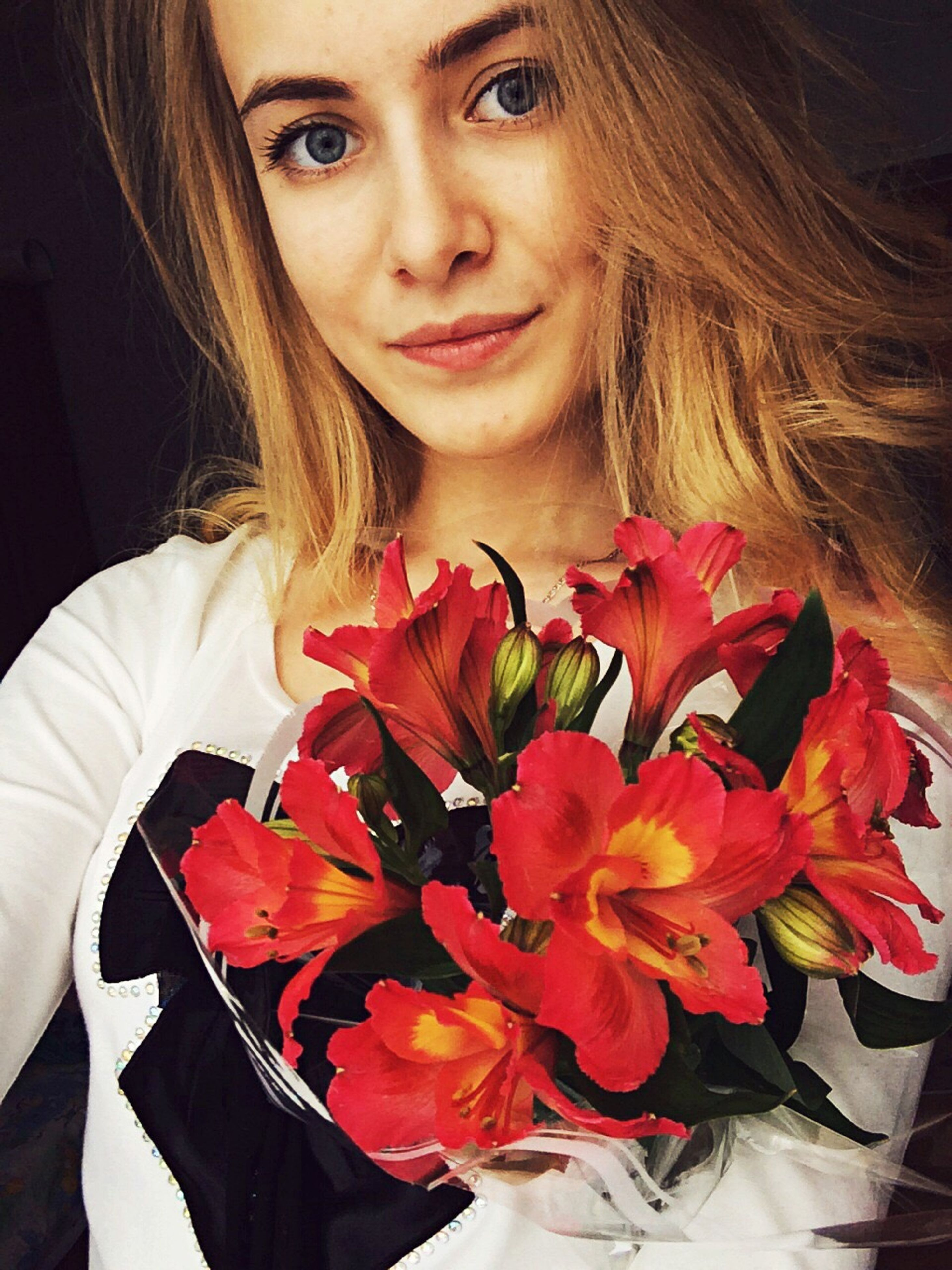 person, young women, lifestyles, portrait, looking at camera, front view, long hair, casual clothing, young adult, leisure activity, indoors, red, holding, smiling, flower, waist up, close-up