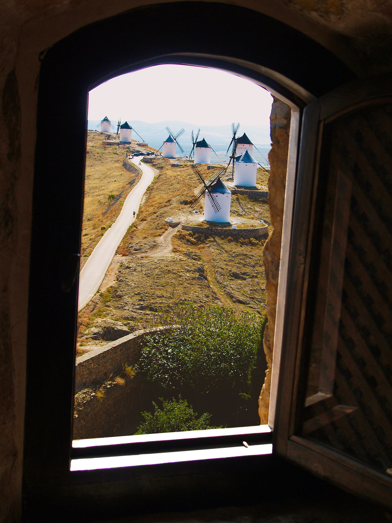 Windmills through a window Arch Clear Sky Day Flying Glass - Material Green Color Growth In Front Of Indoors  La Mancha Landscape Lawn Nature Quijote Sky SPAIN Tranquility Transparent Windmill Windmills Window