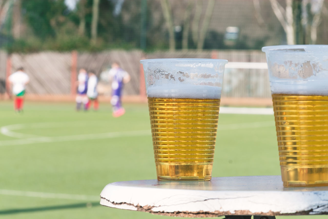 Alcohol Beer Beer Glass Close-up Competition Copy Space Day Drink Drinking Glass Focus On Foreground Food And Drink Football Freshness Frothy Drink Leisure Activity Outdoors People Refreshment Soccer Field Spectator Table