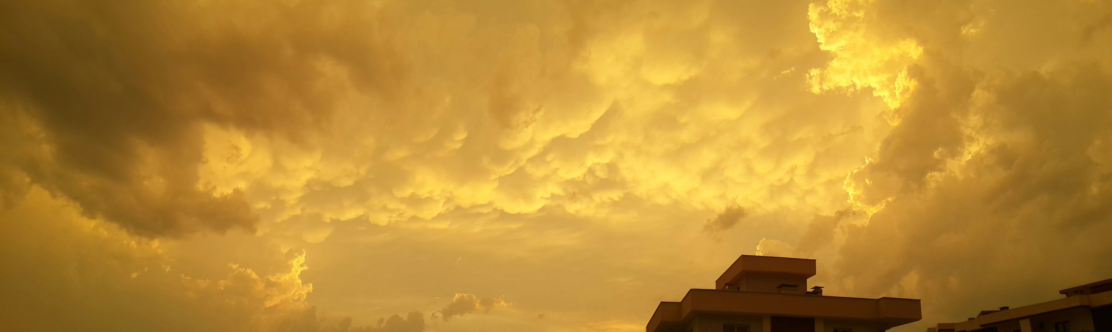 sunset, sky, cloud - sky, orange color, scenics, beauty in nature, cloudy, building exterior, architecture, built structure, dramatic sky, low angle view, cloud, silhouette, nature, tranquility, tranquil scene, idyllic, cloudscape, weather