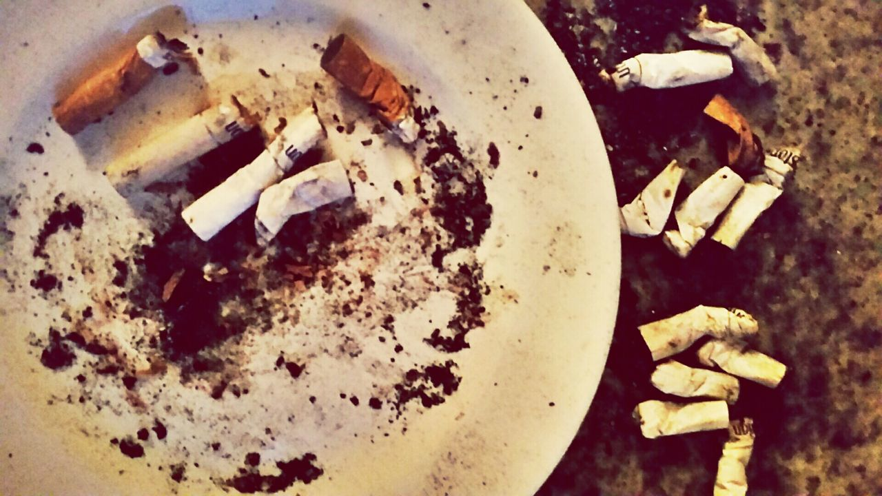 Close-Up Of Burnt Cigarette Butts In Plate
