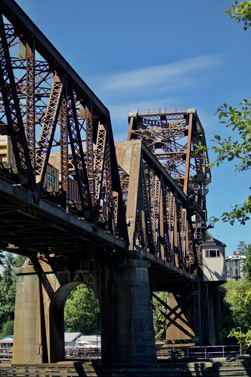 bridge - man made structure, connection, built structure, architecture, engineering, transportation, low angle view, outdoors, railroad bridge, day, sky, bridge, no people, travel destinations, tree