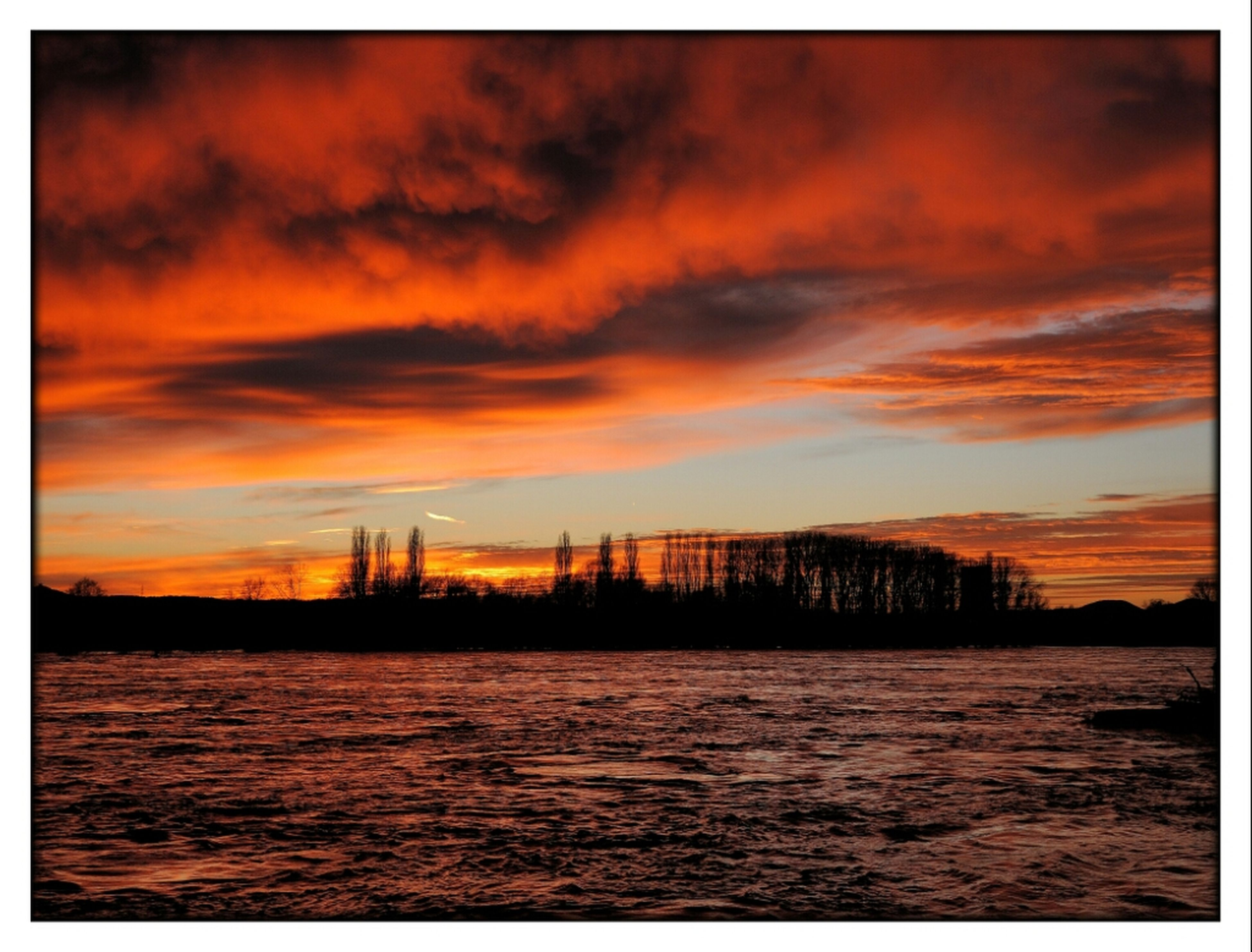 sunset, transfer print, orange color, auto post production filter, sky, water, waterfront, cloud - sky, architecture, built structure, scenics, building exterior, beauty in nature, tranquility, dramatic sky, tranquil scene, silhouette, nature, cloud, river