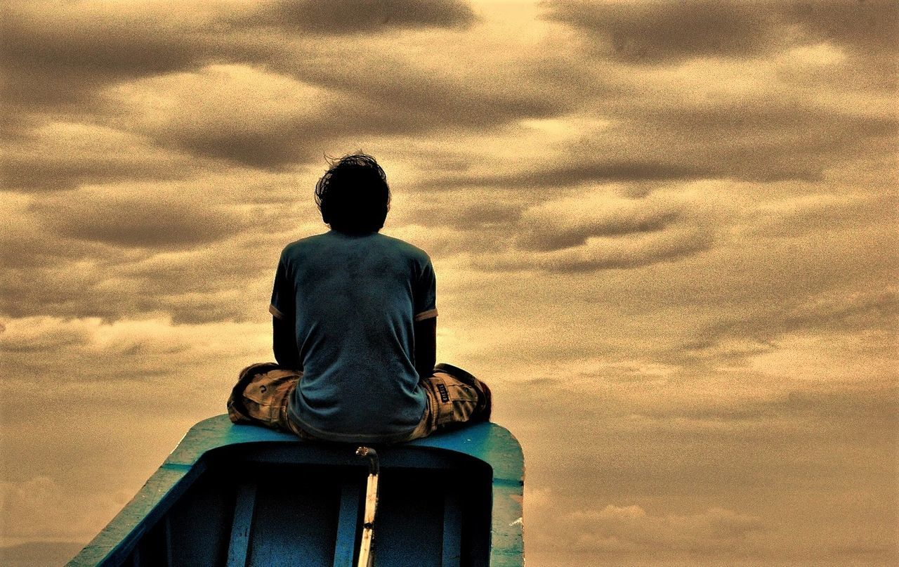 cloud - sky, sky, sitting, rear view, low angle view, one person, sunset, childhood, outdoors, statue, nature, real people, beauty in nature, day, people