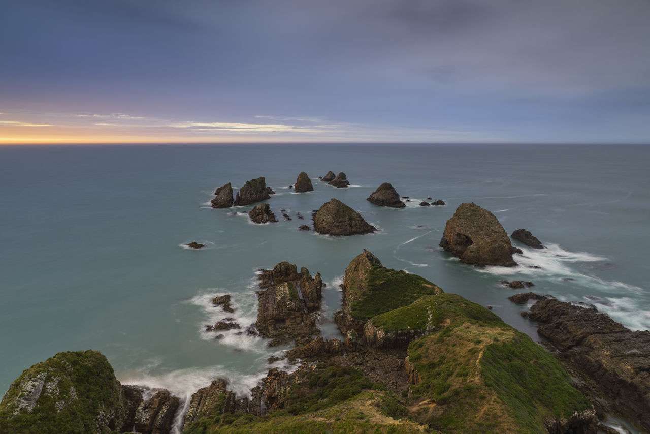 Nugget Point is one of the most iconic landforms on the Otago coast. Located at the northern end of the Catlins coast, along the road from Kaka Point, this steep headland has a lighthouse at its tip, surrounded by rocky islets (The Nuggets). The point is home to many seabirds, including penguins, gannets and royal spoonbills, and a large breeding colony of fur seals. Roaring Bay, on the south coast of the tip of Nugget Point, is home to a small colony of yellow-eyed penguins. Breathtaking Catlins Coast Cliff Flower Kaka Point Landscape Love Nature New Zealand New Zealand Beauty New Zealand Landscape New Zealand Must Do New Zealand Natural New Zealand Scenery Nzmustdo Photography Sea Sea And Sky Seascape Sony Sony A6000 Sony Japan Sonyalpha South New Zealand Sunrise