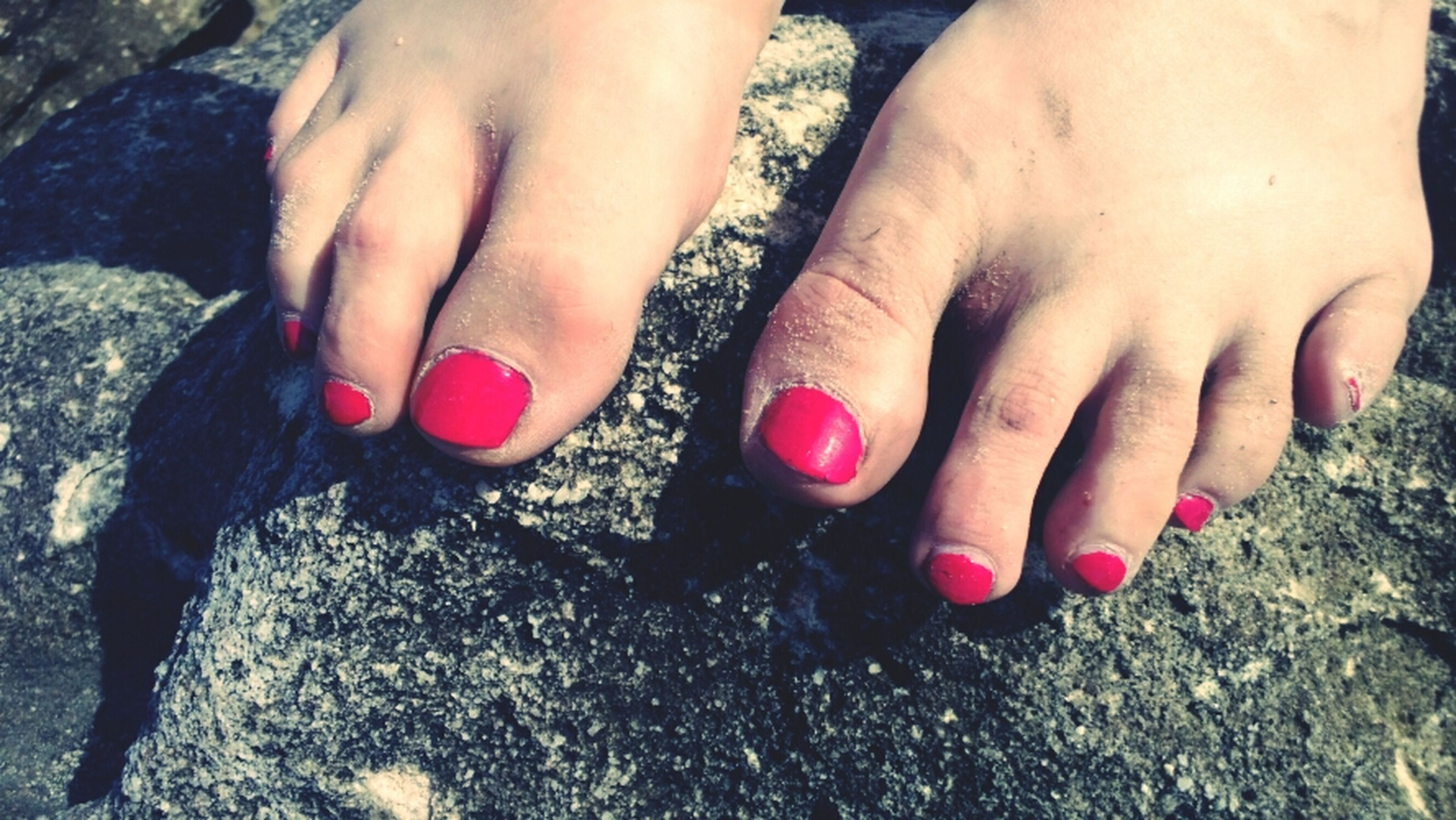 Symbols of summer: sandy toes with red toenails