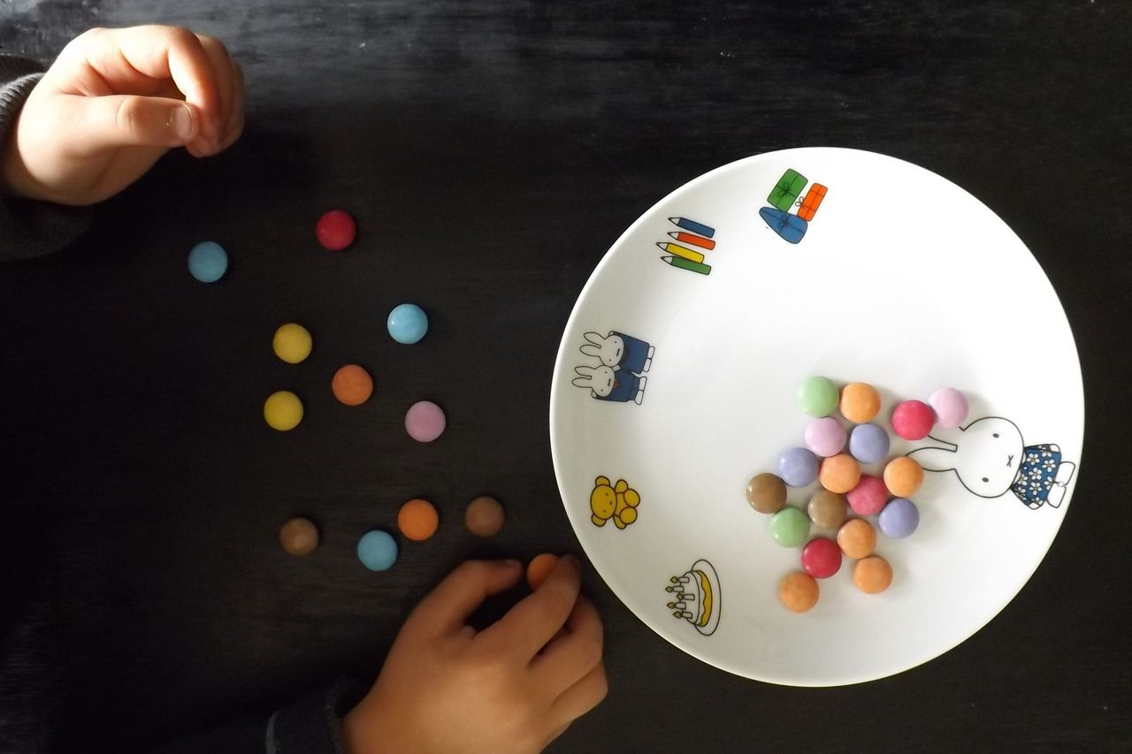 Adult Assiette Bonbons Child Close-up Day Dessin Doigts Enfance Enfant Fond Noir Food Human Body Part Human Hand Indoors  Main Multi Colored One Person People Sweet Food Table