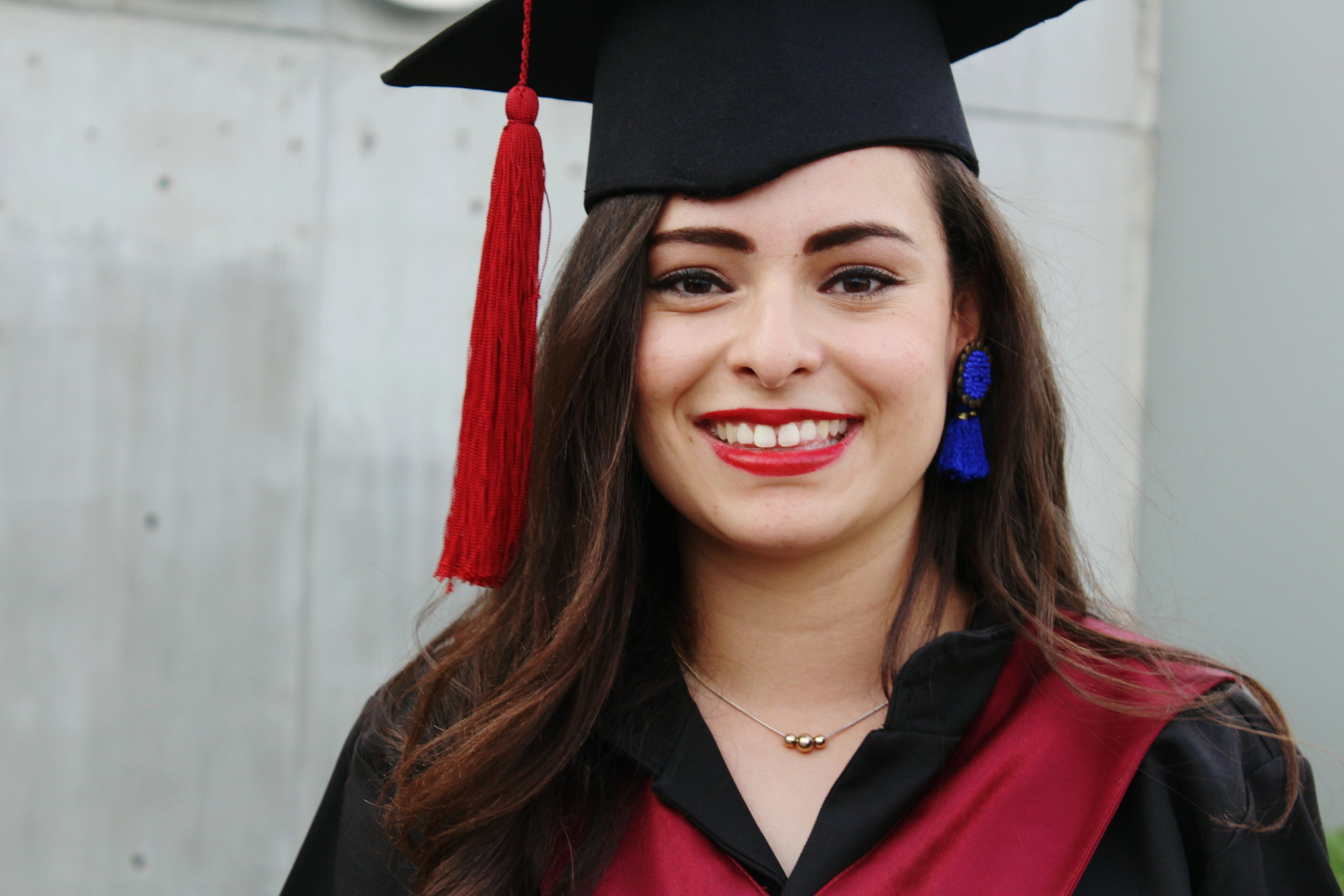 graduation gown, graduation, mortarboard, achievement, young adult, real people, young women, happiness, one person, front view, headshot, education, smiling, standing, celebration, portrait, lifestyles, looking at camera, red, cheerful, beautiful woman, life events, university student, medium-length hair, outdoors, day, close-up