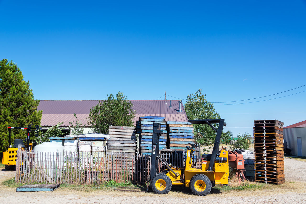 BUFFALO, WY - AUGUST 22: Palettes and machinery used in beekeeping in Buffalo, WY on August 22, 2015 Apiary APIculture Bee Beehive Beehives Bees Box Boxe Buffalo Clear Sky Day Hive Machine Machinery No People Outdoors Palette Palettes Sky Tractor USA Wyoming