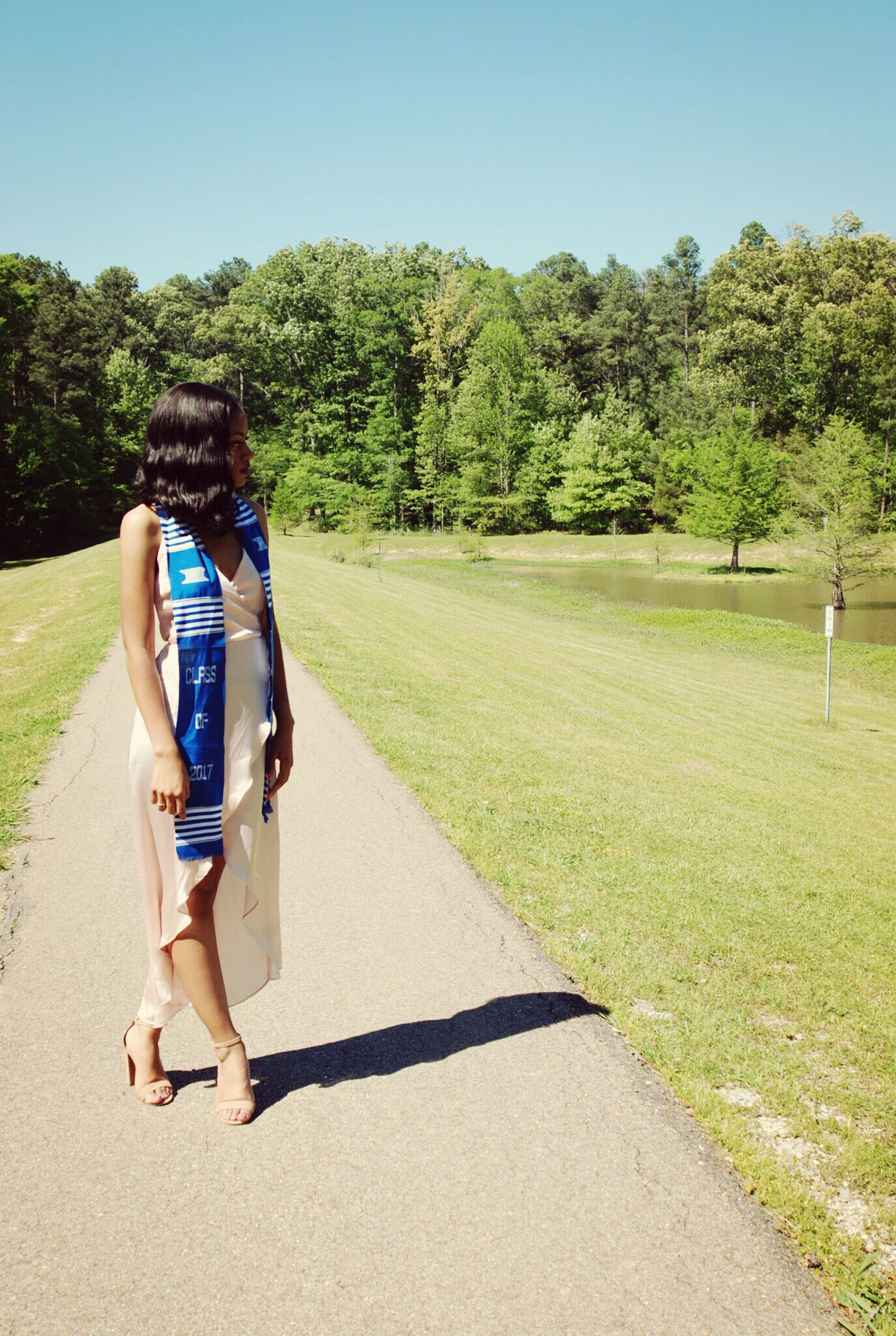 tree, rear view, full length, walking, day, casual clothing, leisure activity, clear sky, real people, outdoors, nature, sunlight, one person, grass, lifestyles, road, shadow, beauty in nature, scenics, sky, young adult, people