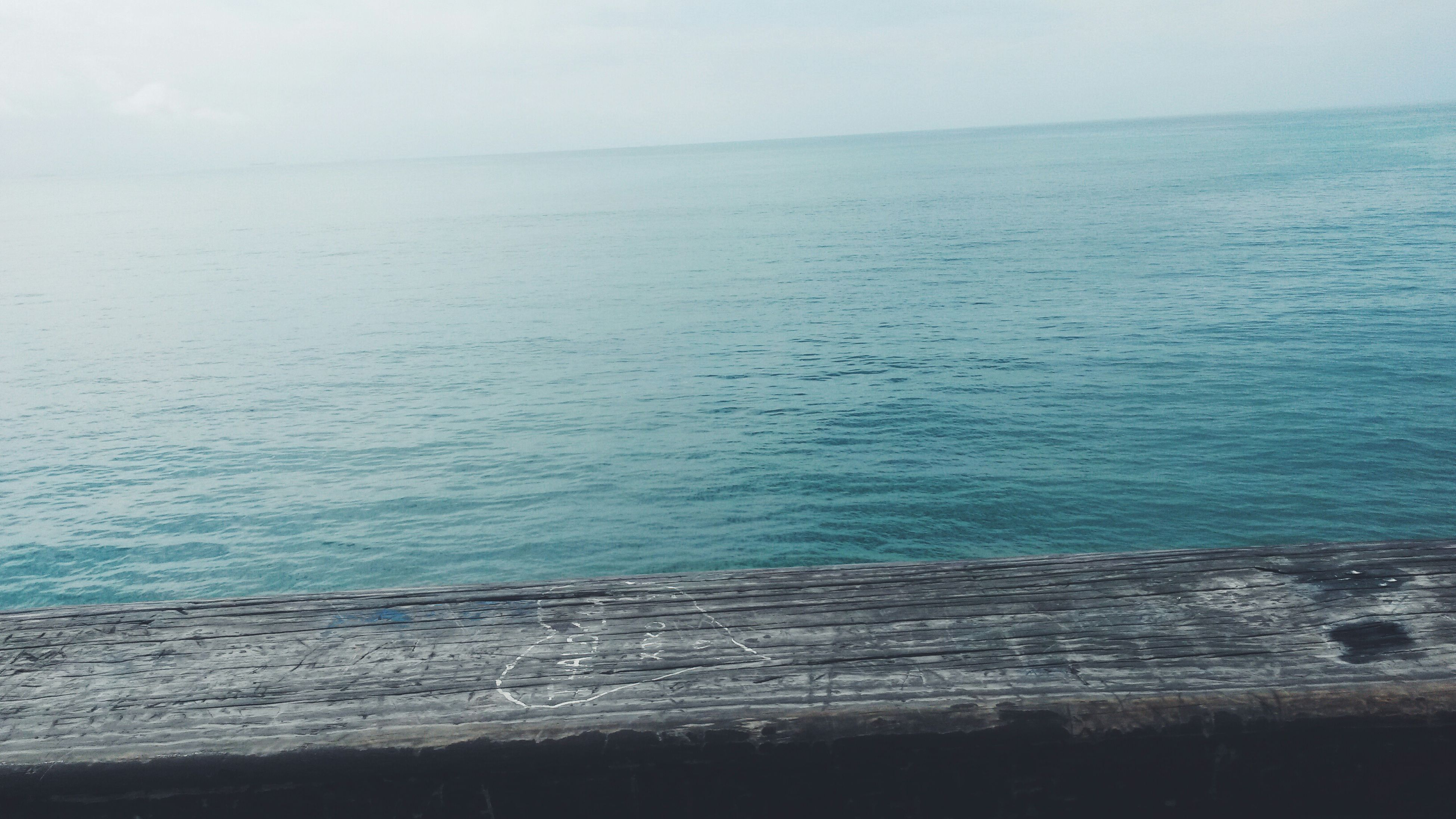 sea, water, horizon over water, tranquil scene, tranquility, scenics, beauty in nature, nature, blue, copy space, sky, seascape, idyllic, rippled, clear sky, wood - material, calm, day, pier, high angle view